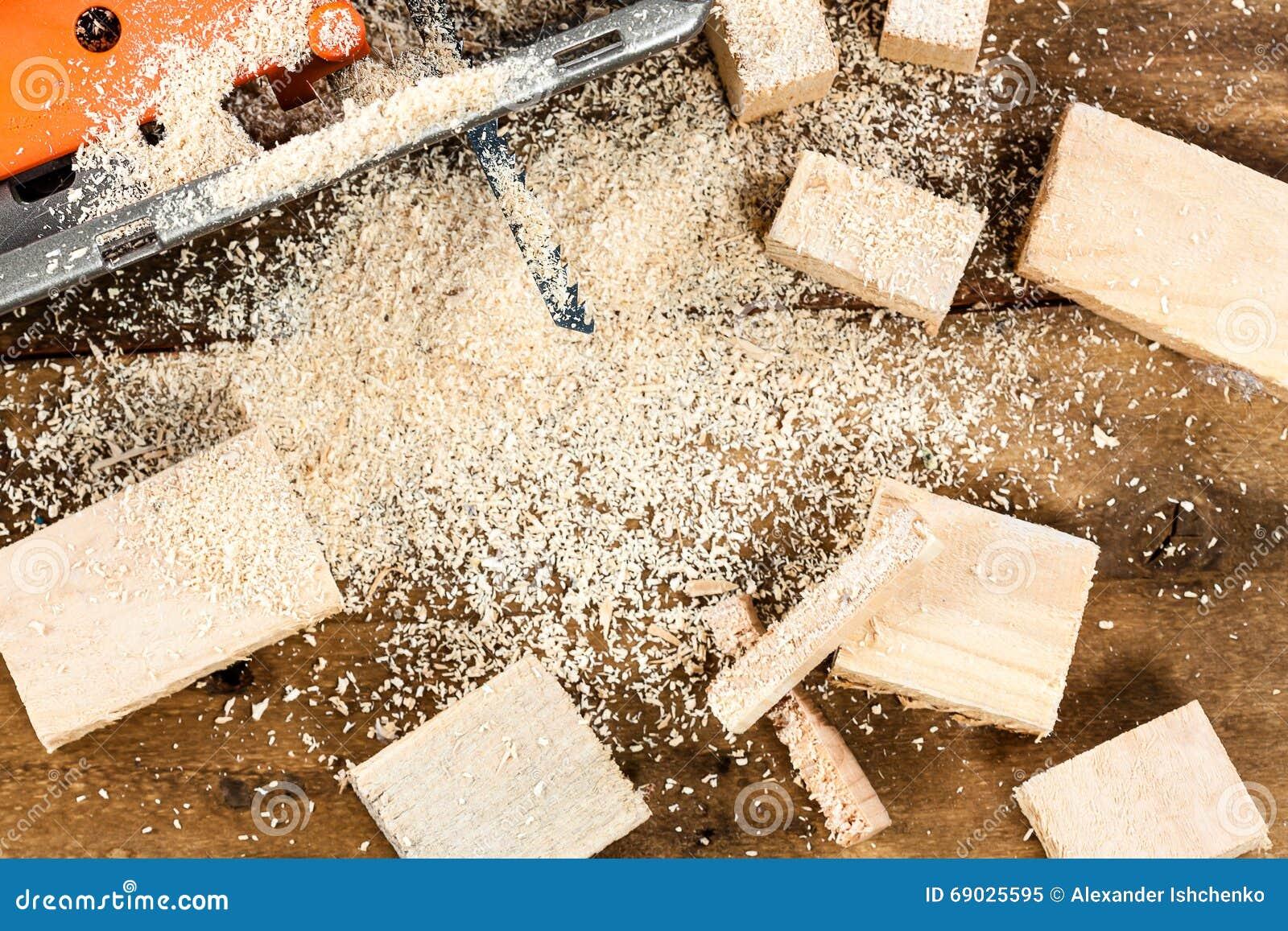 有许多木砖的电竖锯有很多在老被抓的木桌,工作上的锯木屑用工具加工图片
