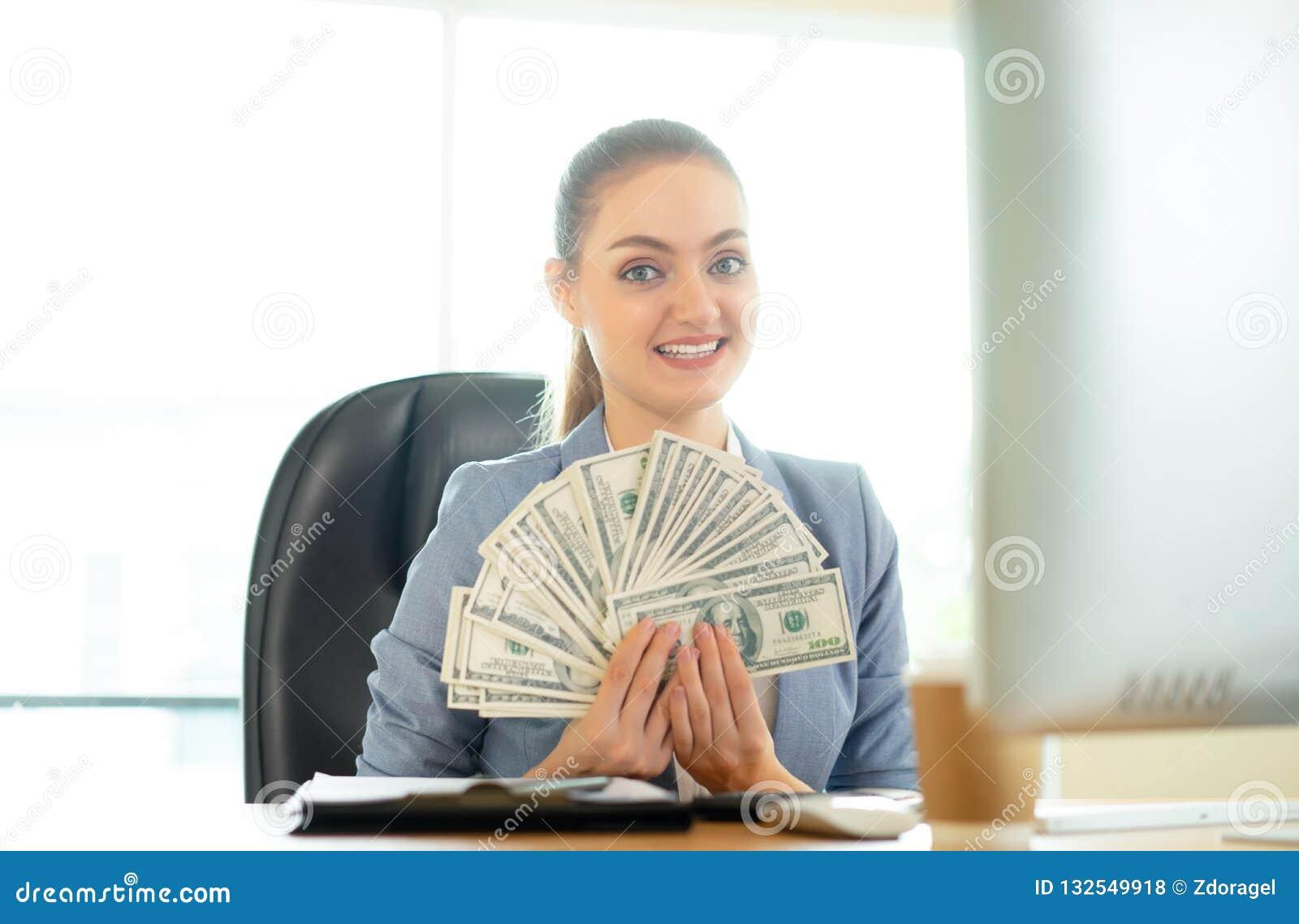 有许多美元的愉快的深色的妇女在膝上型计算机附近在办公室