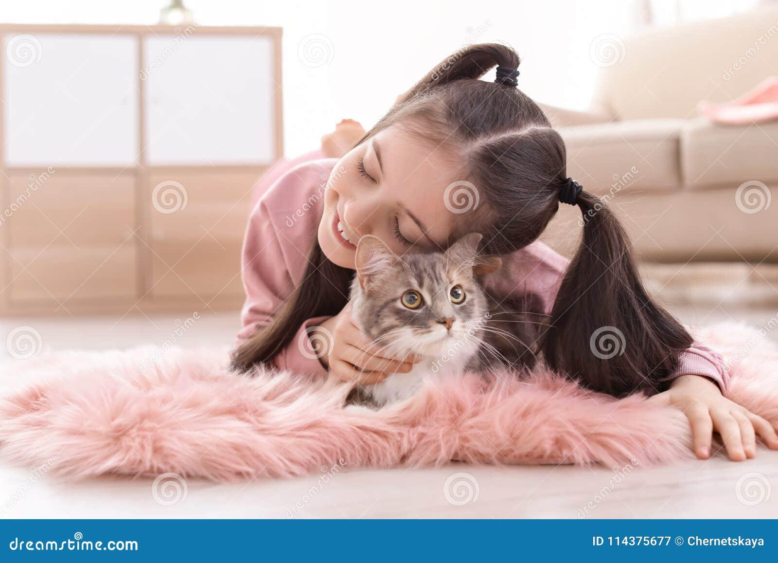 有说谎在地板上的猫的逗人喜爱的小女孩