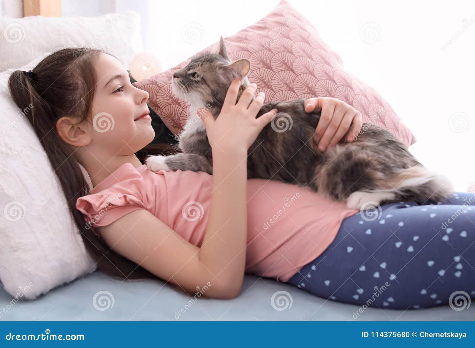 有说谎在床上的猫的逗人喜爱的小女孩