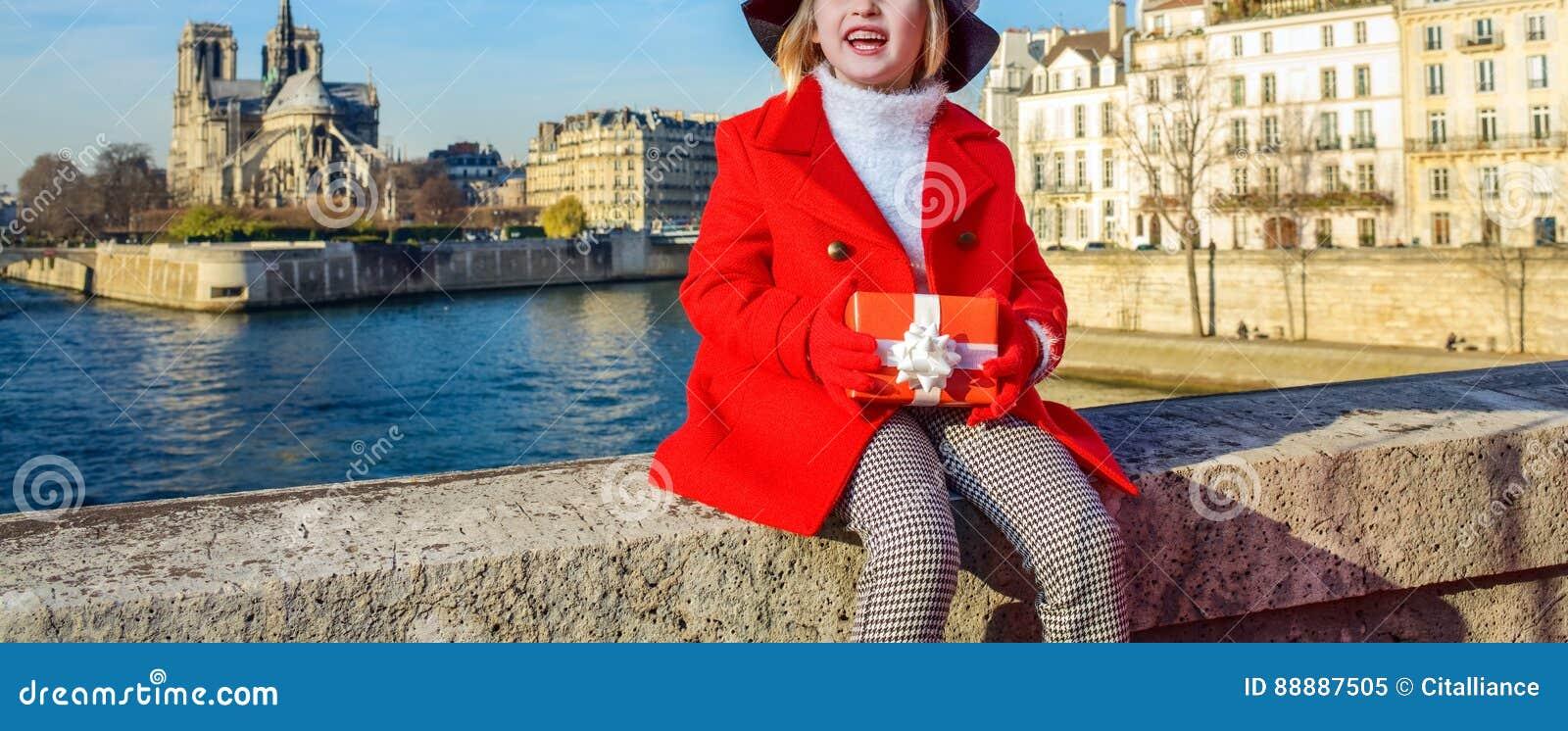 有调查距离的圣诞节礼物箱子的女孩在巴黎
