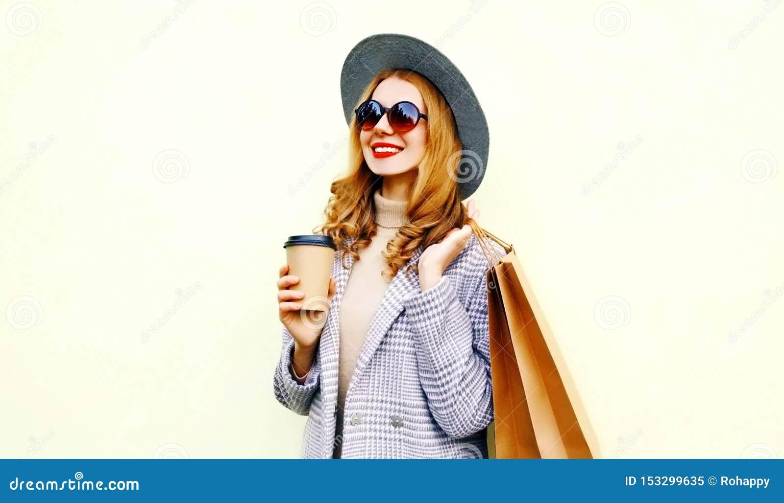 有购物带来和咖啡杯的,佩带的桃红色外套,在背景的圆的帽子画象微笑的妇女