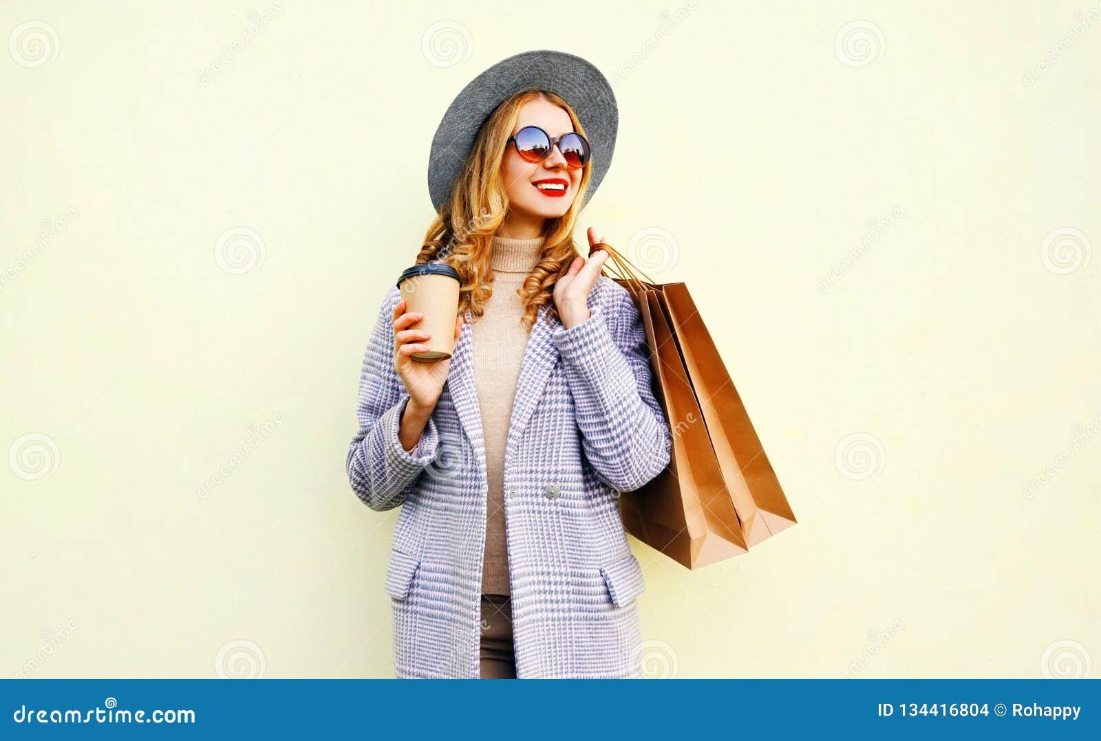 有购物带来的画象俏丽的微笑的妇女,拿着咖啡杯,佩带的桃红色外套,圆的帽子
