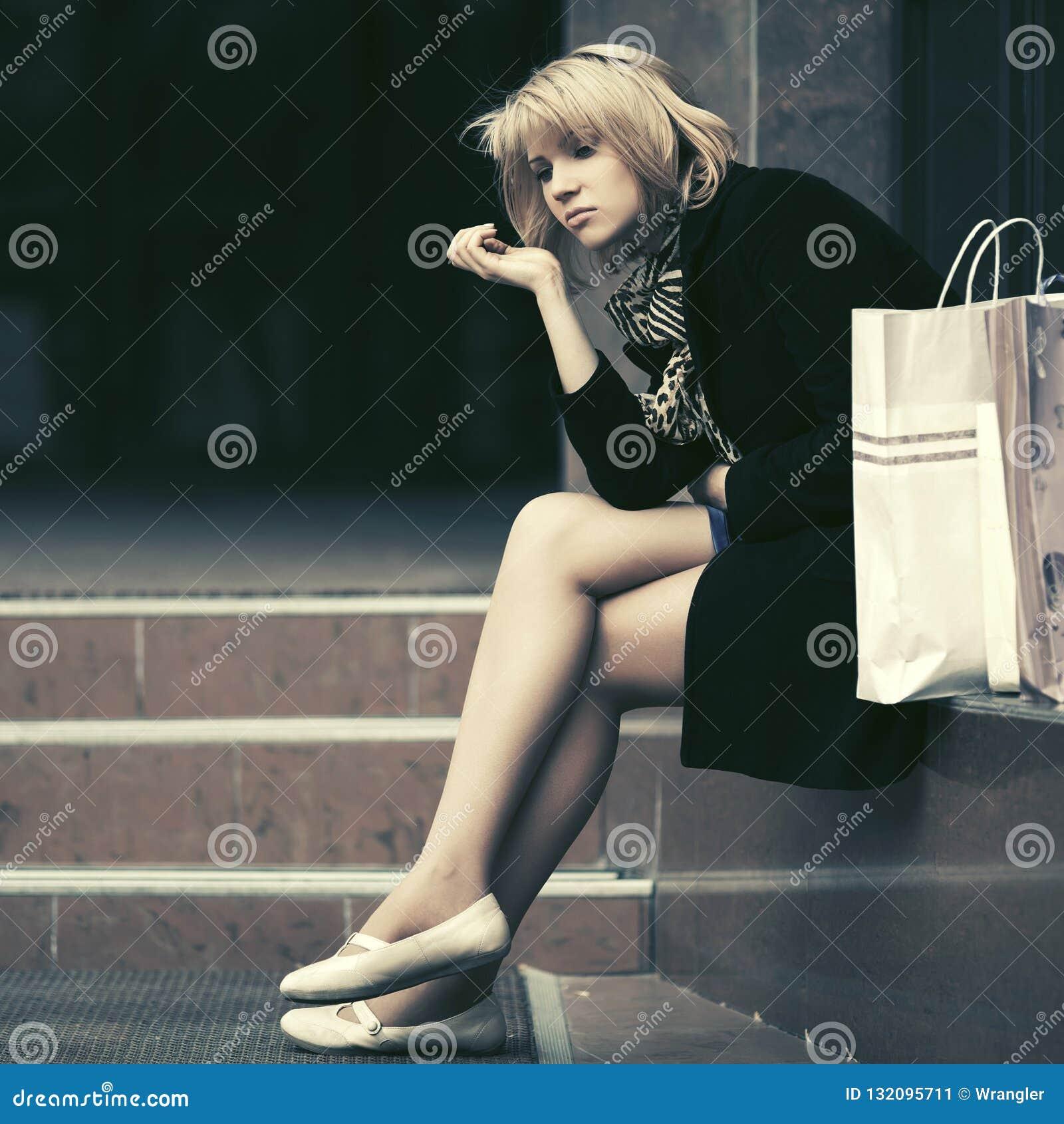 有购物袋的哀伤的少妇坐购物中心跨步