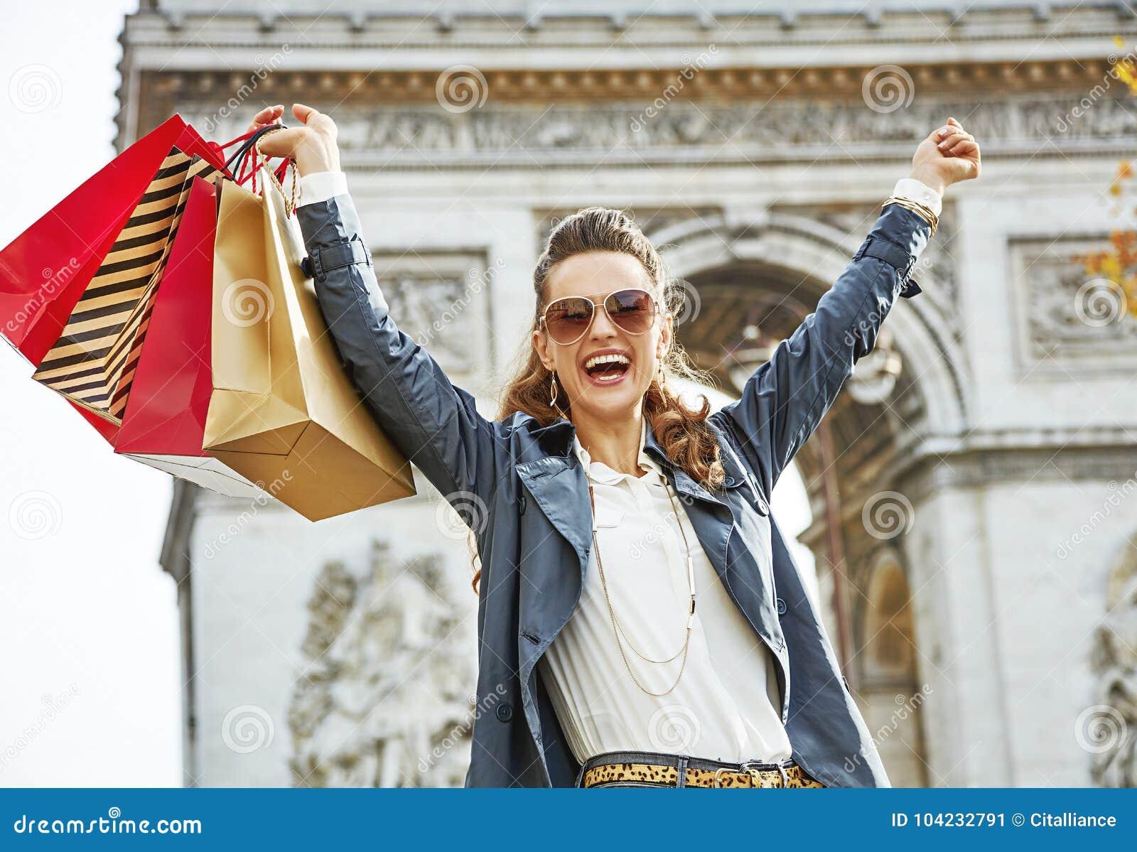 有购物袋的微笑的妇女在巴黎,法国欣喜