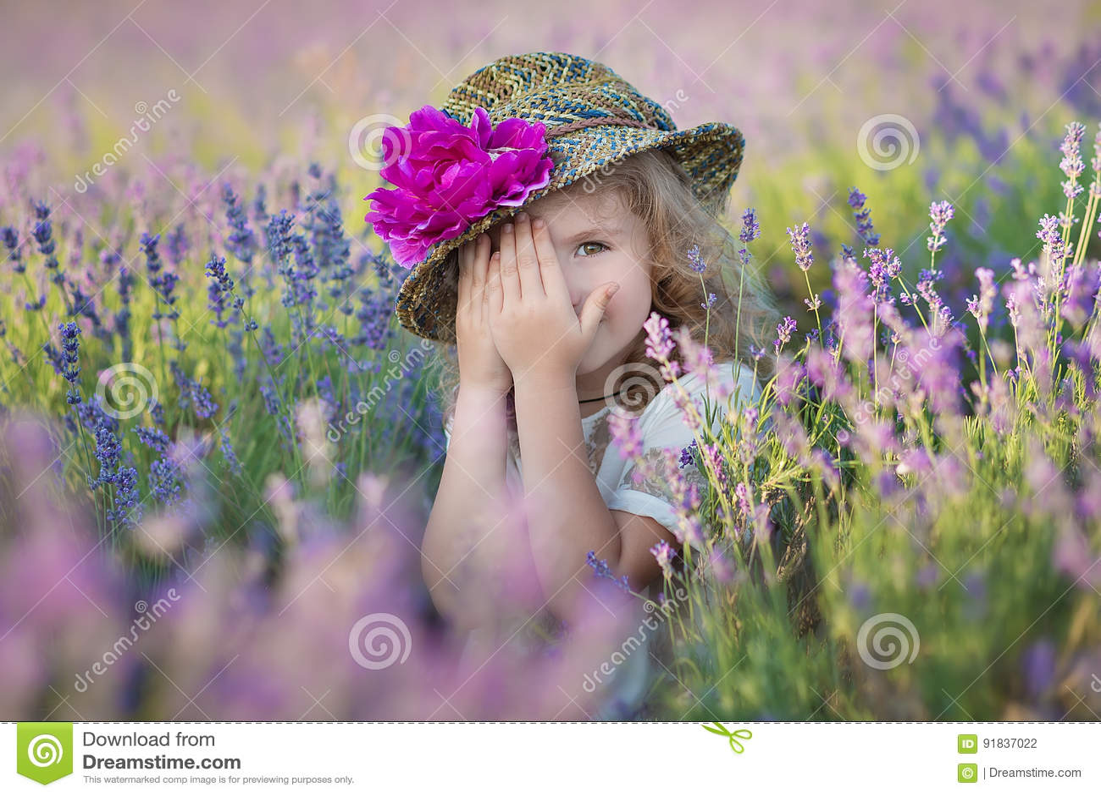 有走在淡紫色领域的可爱的女儿的年轻美丽的夫人母亲在美妙的礼服和帽子的一周末天