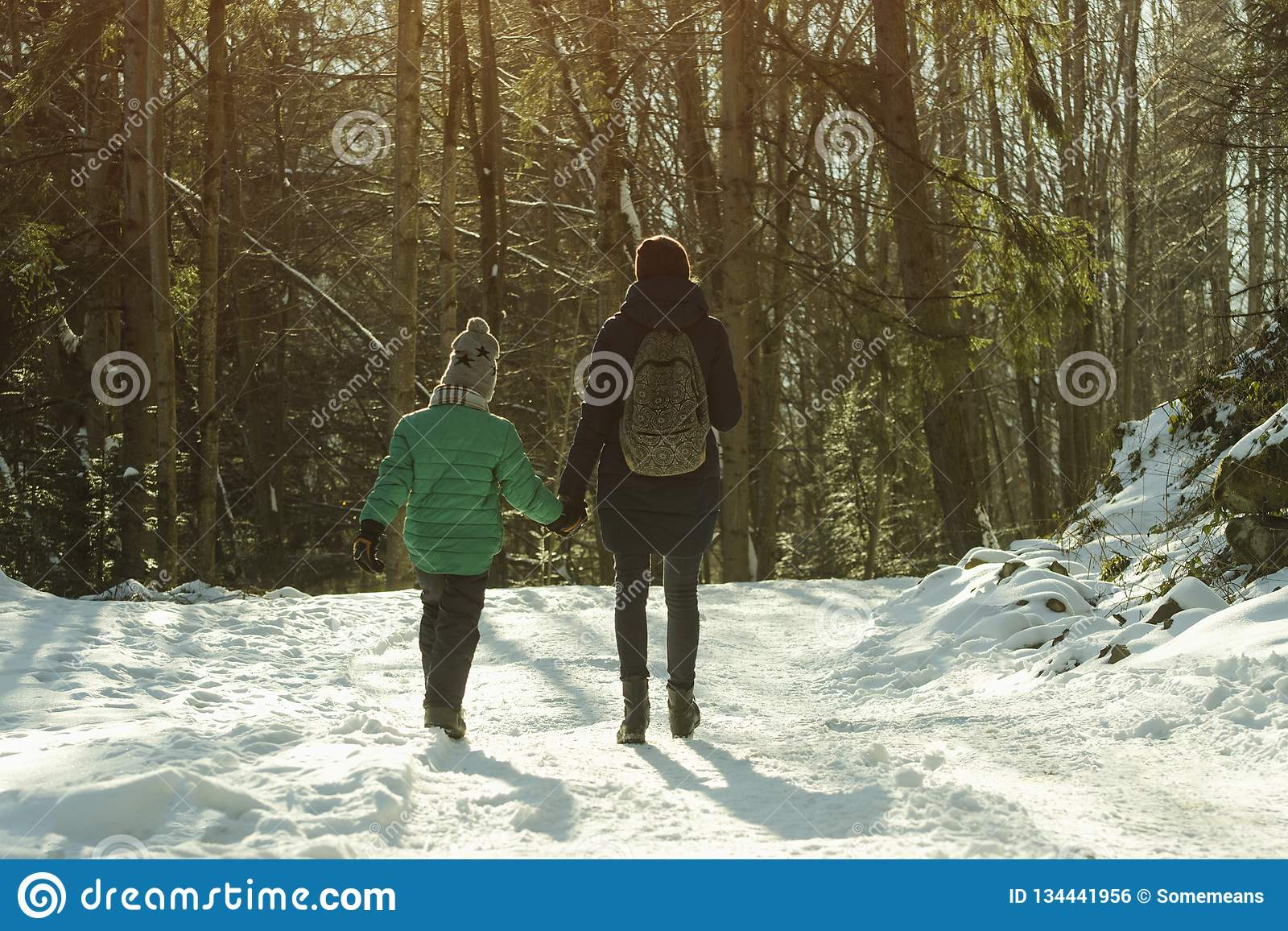 有走沿积雪的路的儿子的母亲以具球果森林冬天好日子为背景