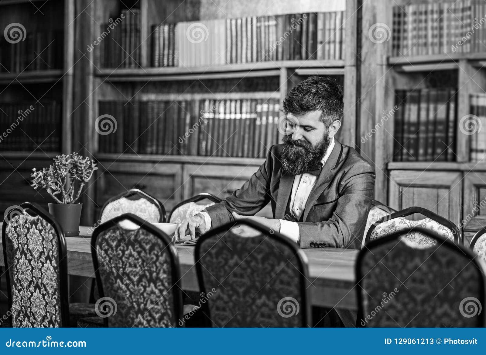 有趣的书概念 愉快的人在内部的葡萄酒坐并且享受松弛读书 正式成套装备的有胡子的人