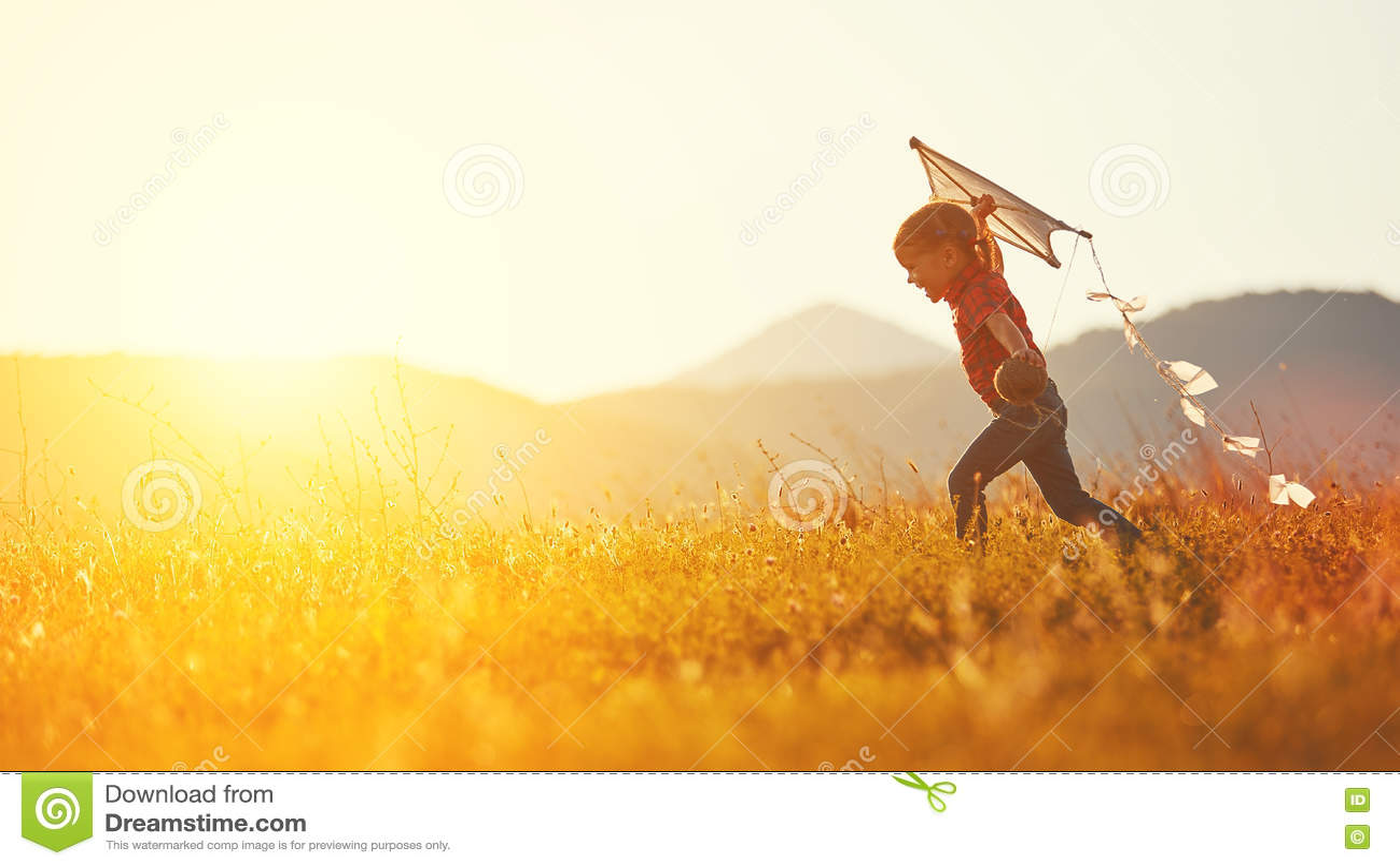 有跑在草甸的风筝的愉快的儿童女孩在夏天