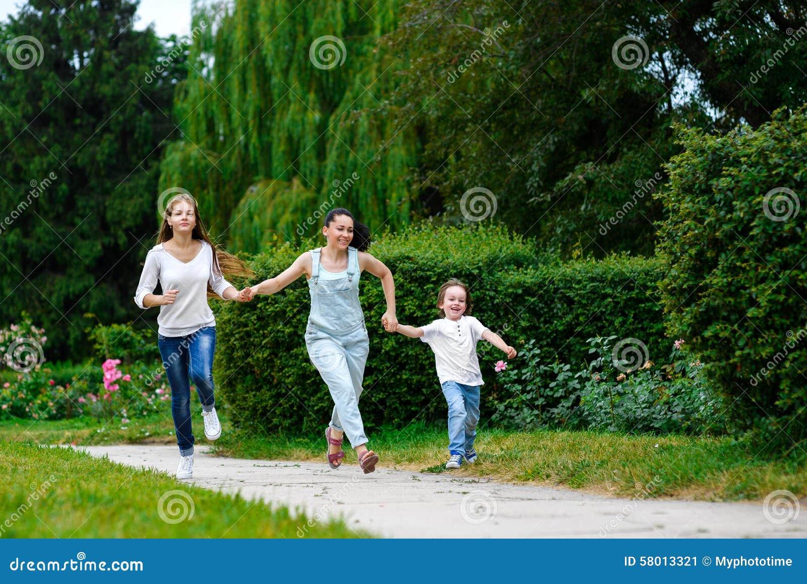 有跑的女儿和的儿子的愉快的母亲