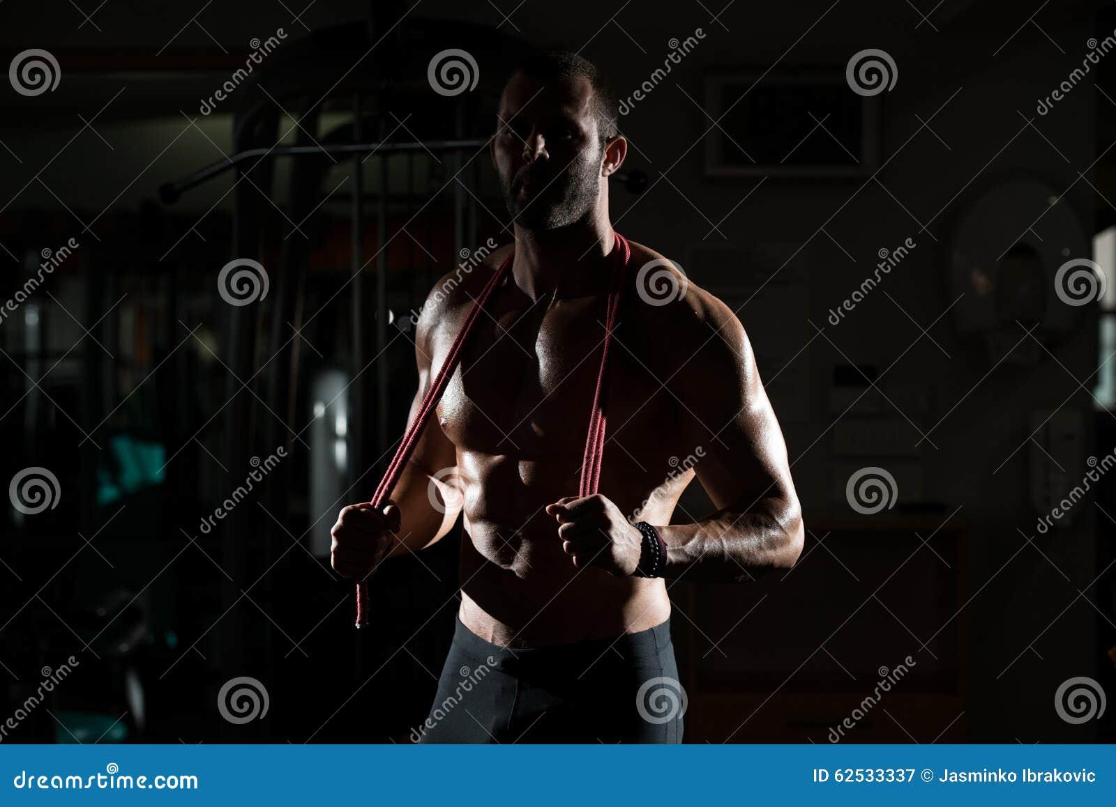 有跳绳的年轻肌肉人在Siluet