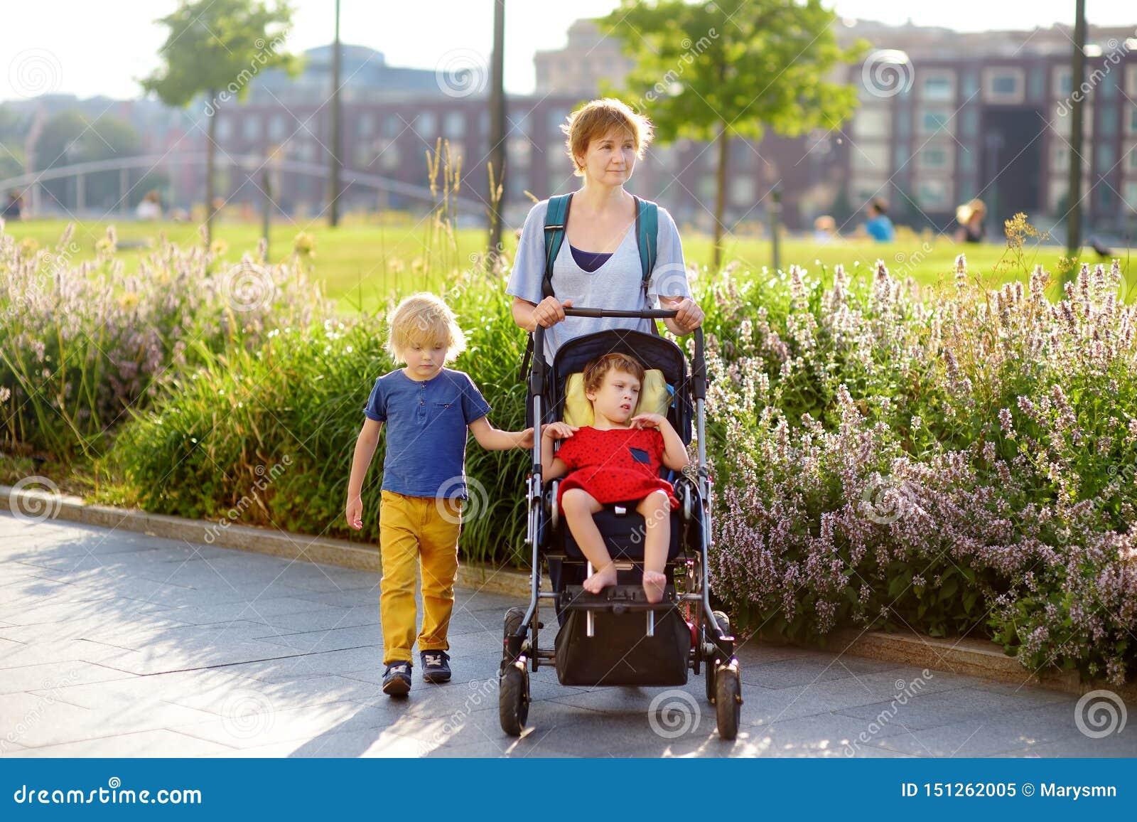 有轮椅的走在公园的一个男孩和一个残疾女孩的妇女在夏天 儿童大脑麻痹 与残疾孩子的家庭