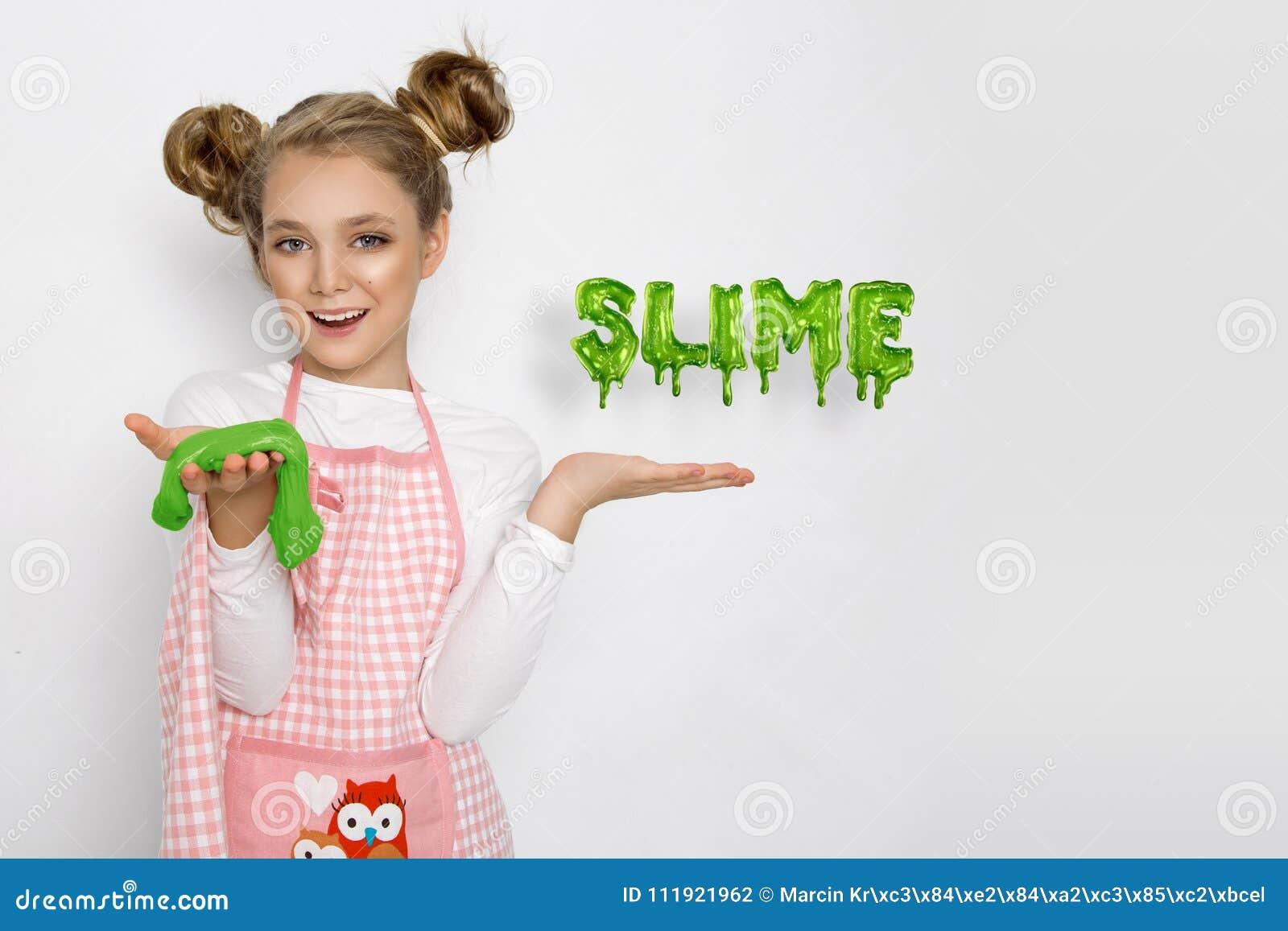 有软泥的逗人喜爱的滑稽的女孩在厨房里 女孩烹调并且烘烤她的松饼,做蛋糕和软泥