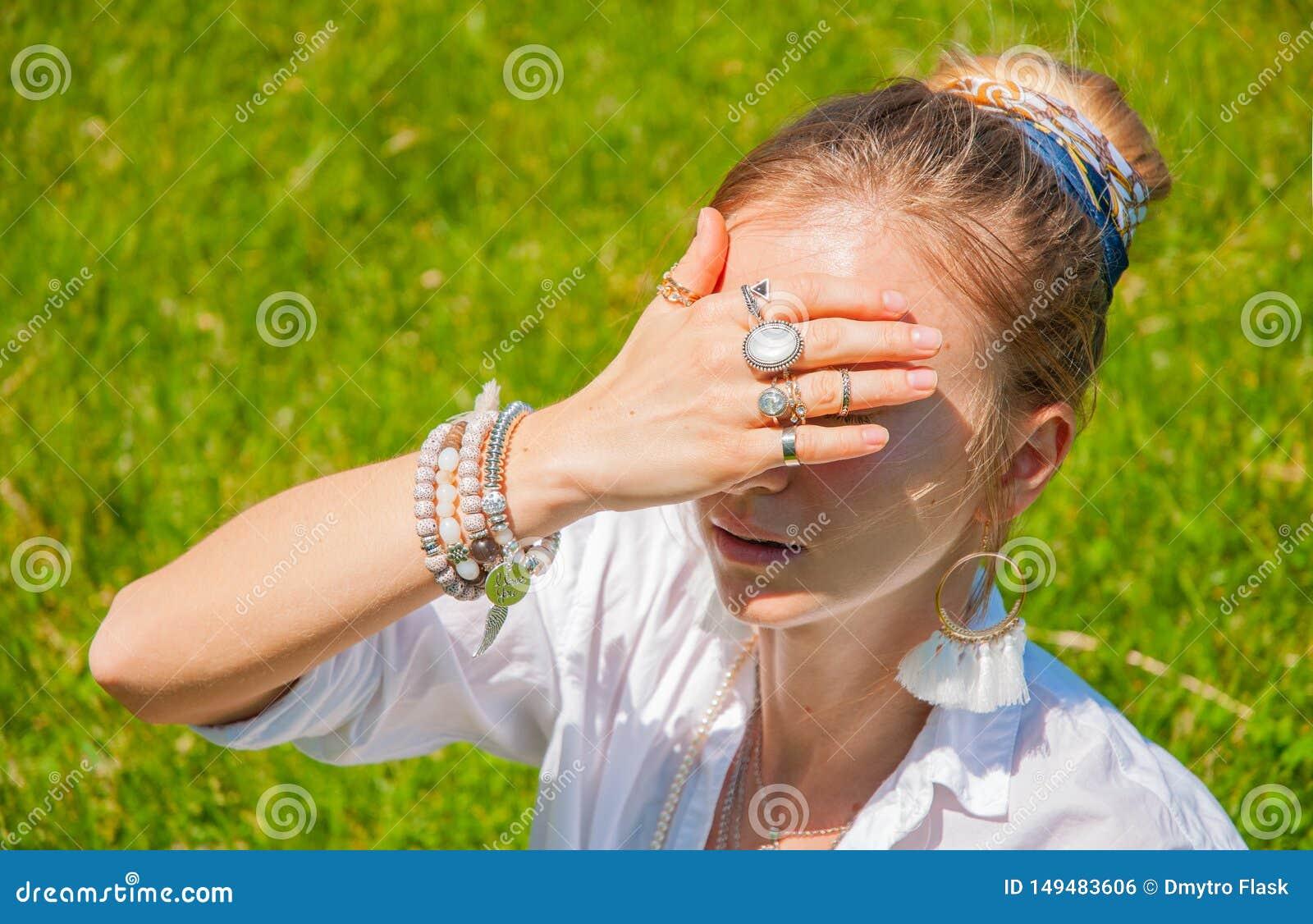 有辅助部件的美丽的boho样式妇女在公园享受夏天好日子 有镯子和圆环的女性手