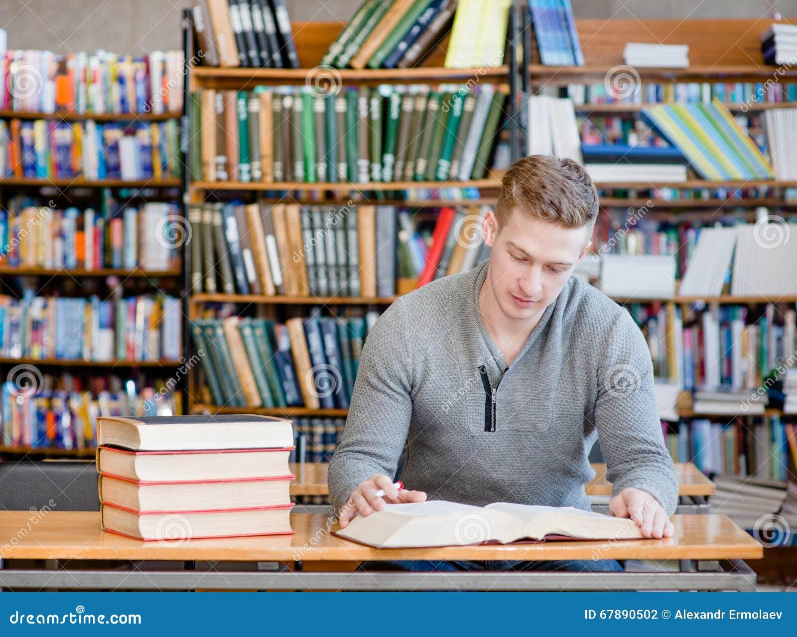 有运作在图书馆里的开放书的男学生