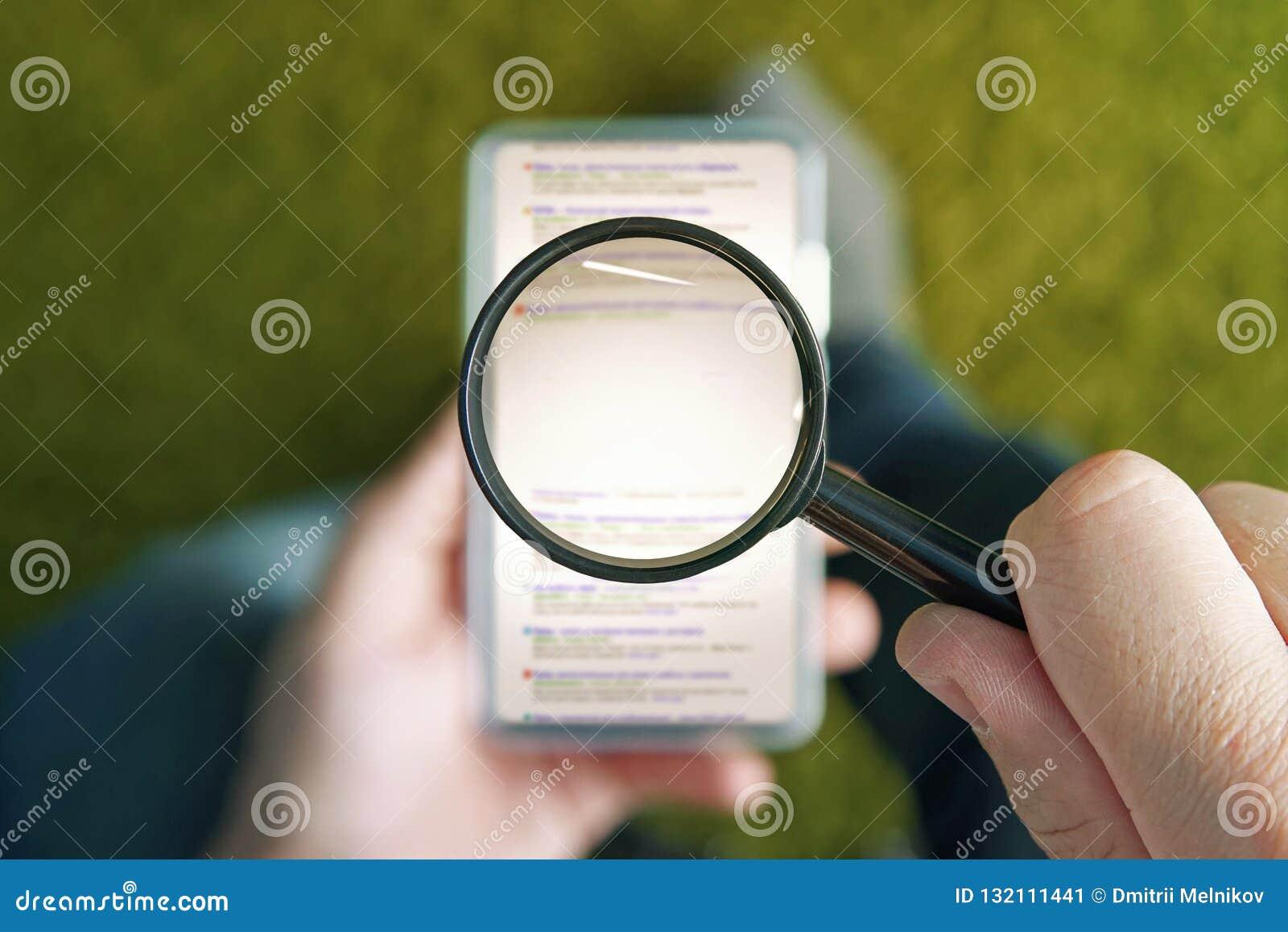 有透明放大器的坐的人在智能手机浏览搜索引擎页上 您的词的拷贝空间