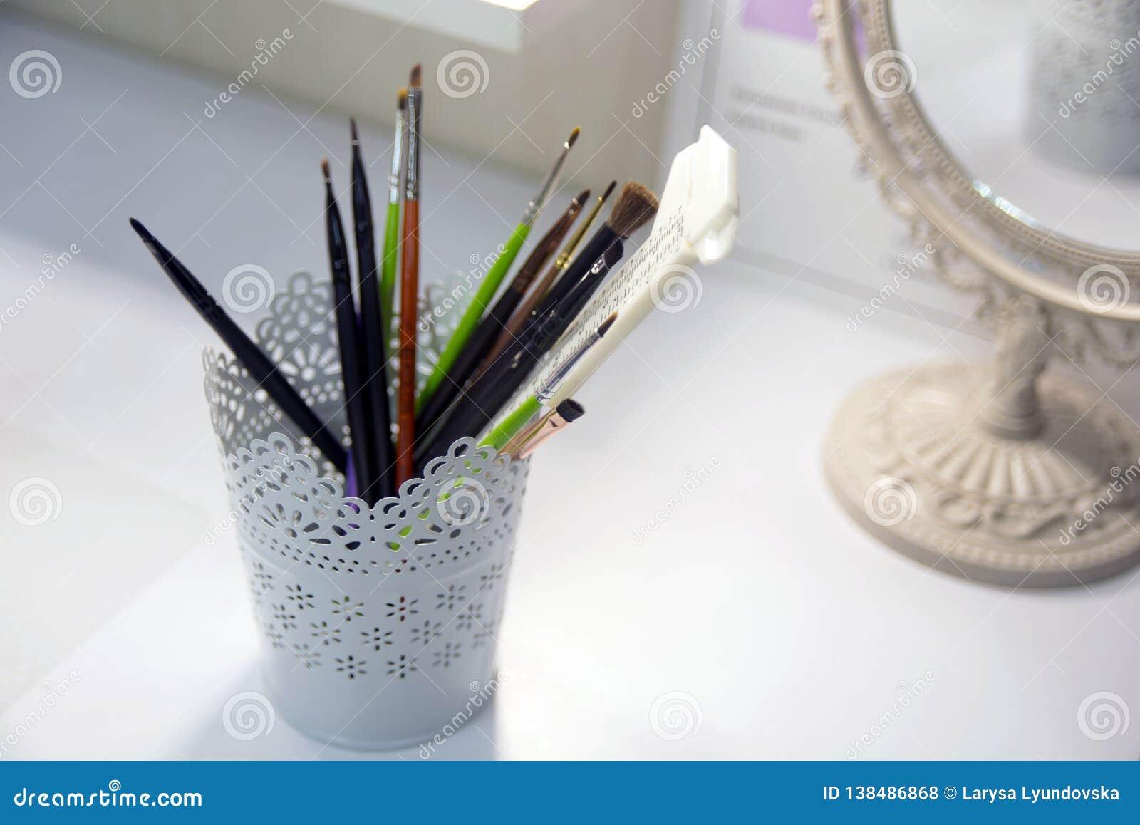 有透雕细工样式的一个美丽,白色杯子存放的刷子为组成