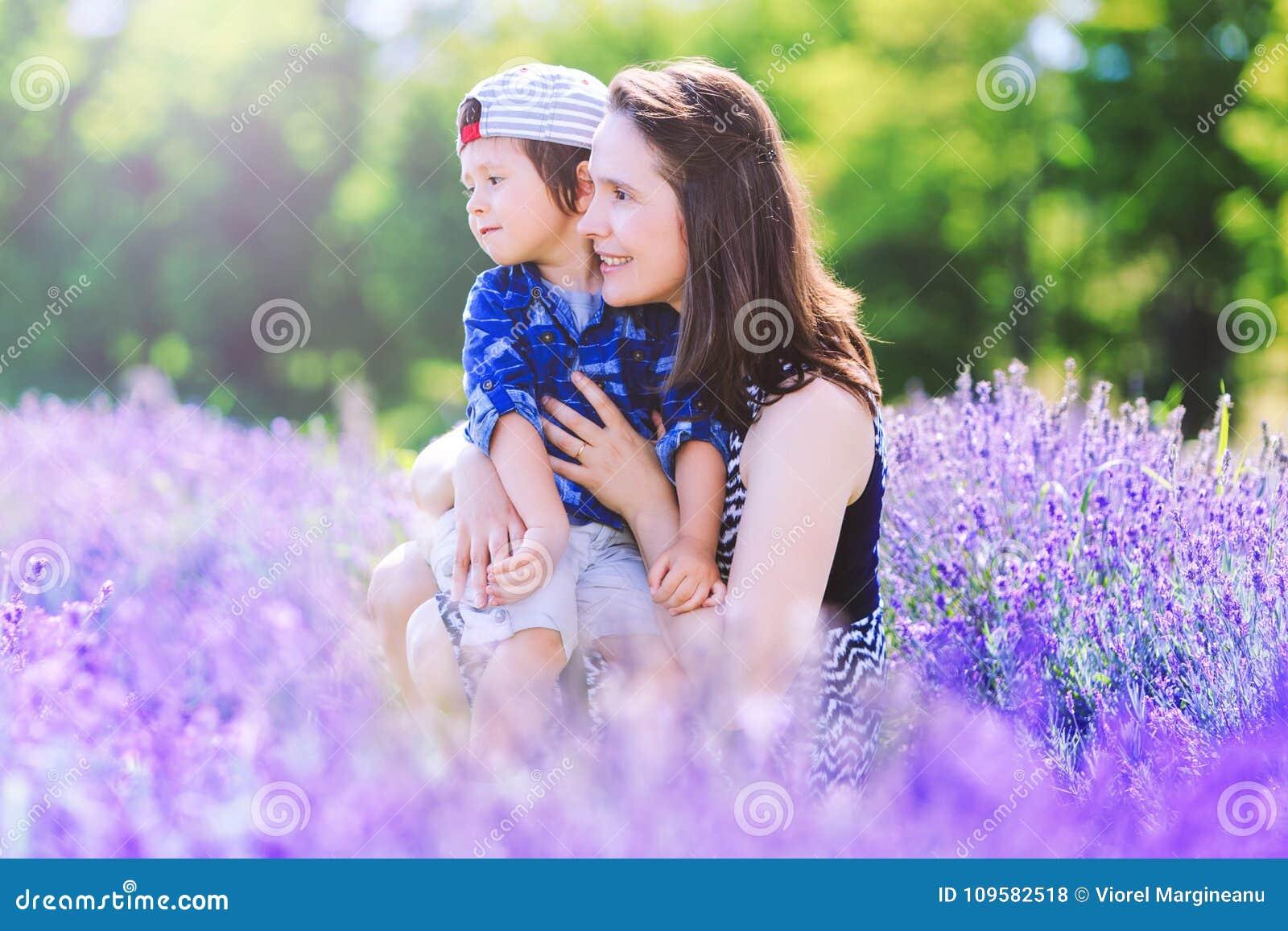 有逗人喜爱的男孩的愉快的妇女淡紫色背景的
