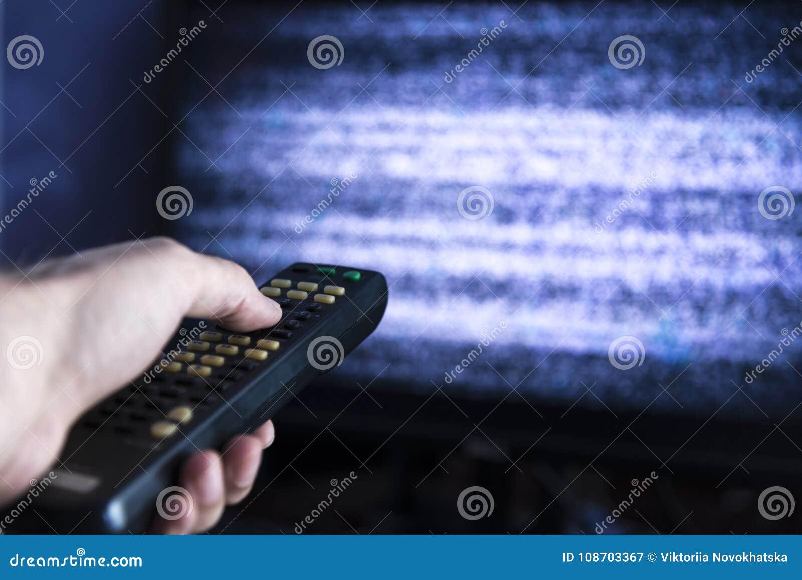 有遥控的男性手从电视