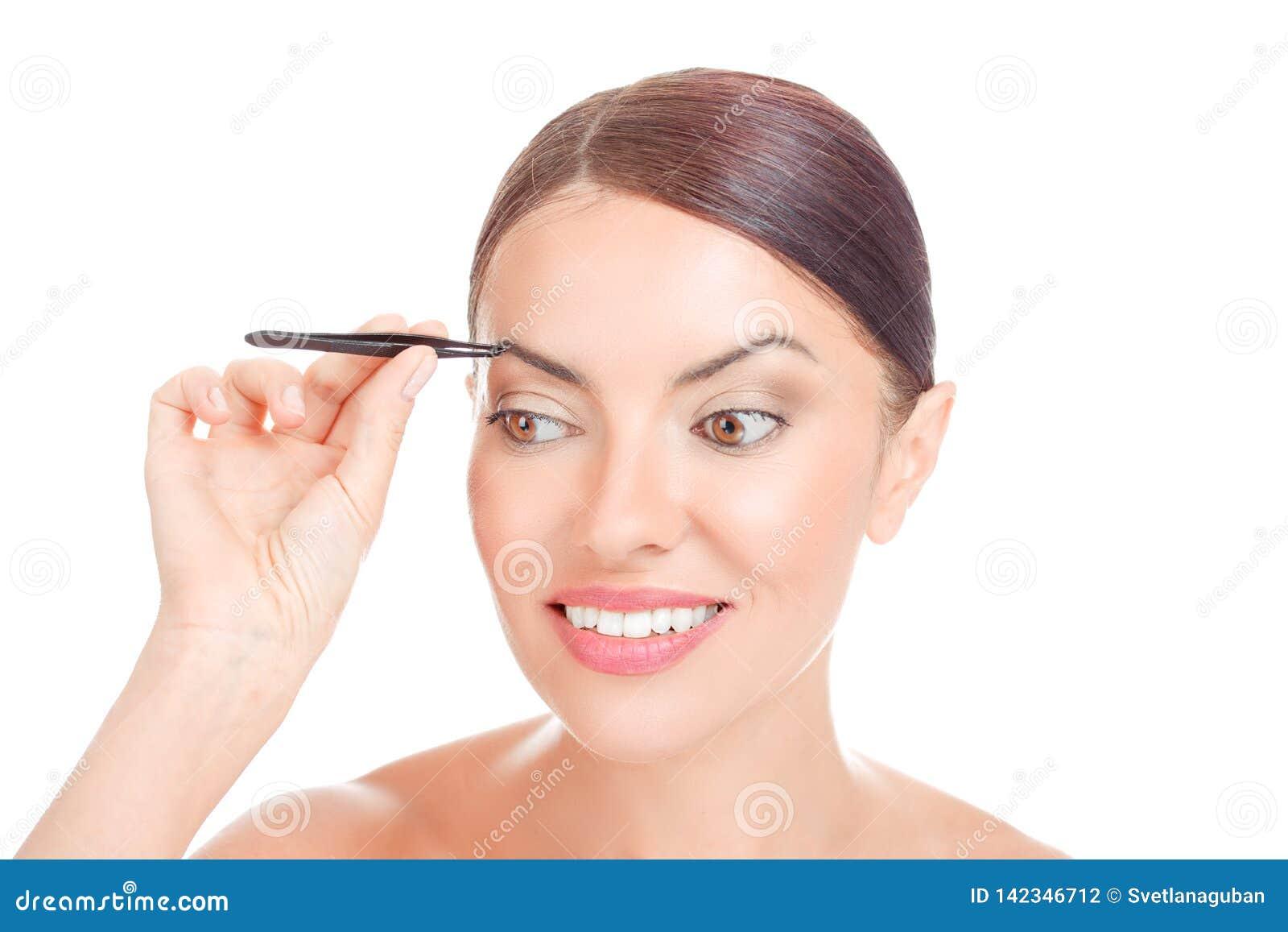 有采有镊子的短发的妇女眼眉