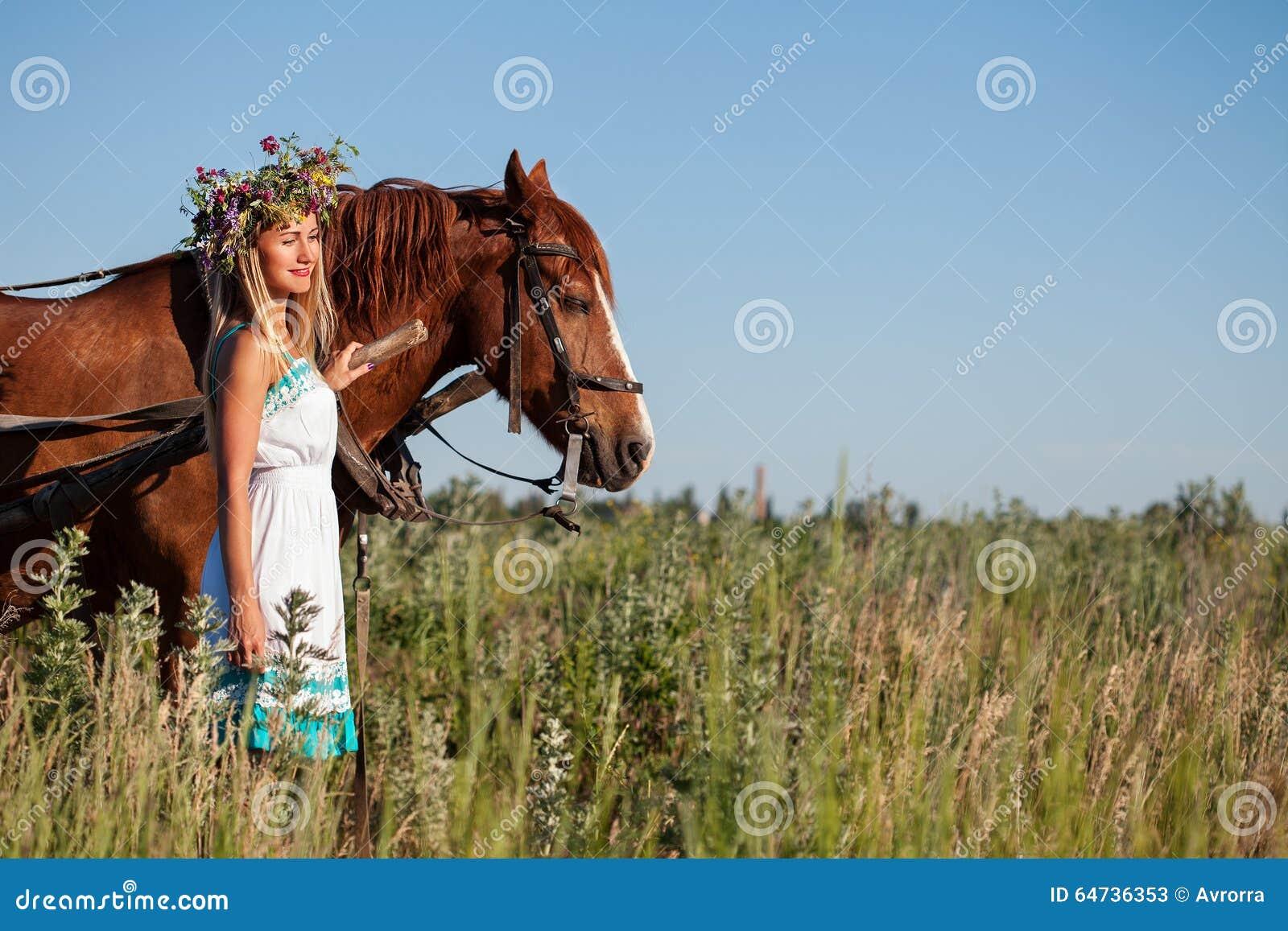 有野花的俏丽的女孩在马支架在夏日