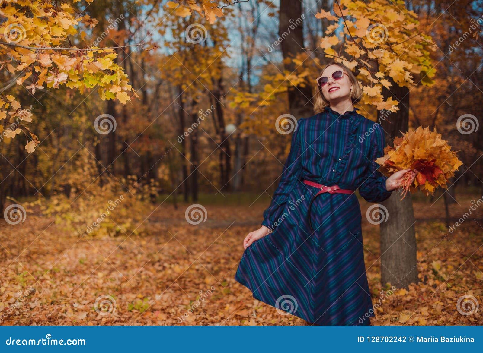 有金发的少妇穿蓝色礼服走在秋天公园的