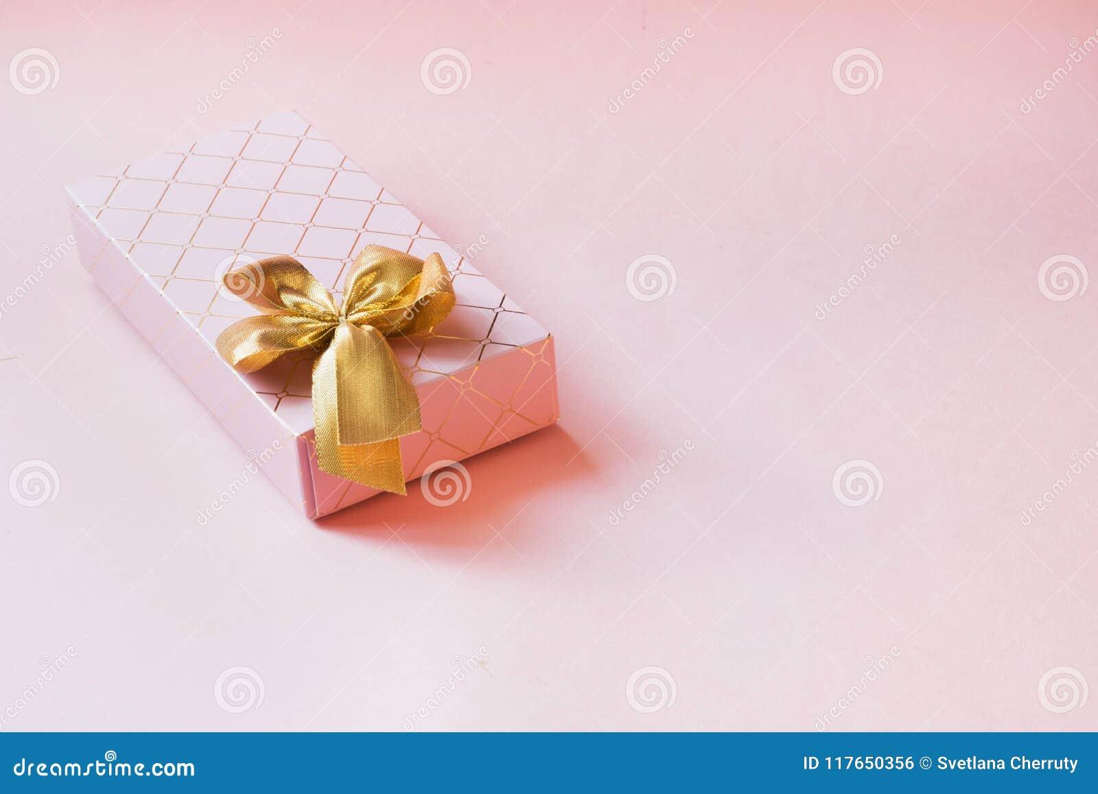 有金黄丝带的女性礼物盒在有魄力的粉红彩笔 生日 复制空间