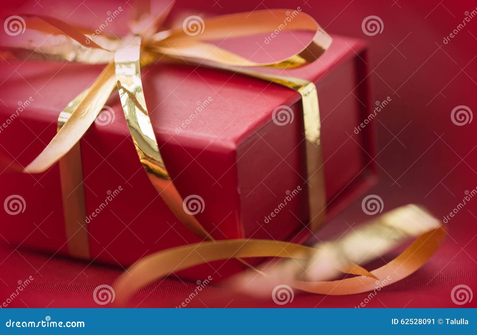 有金黄丝带的红色礼物盒在红色背景