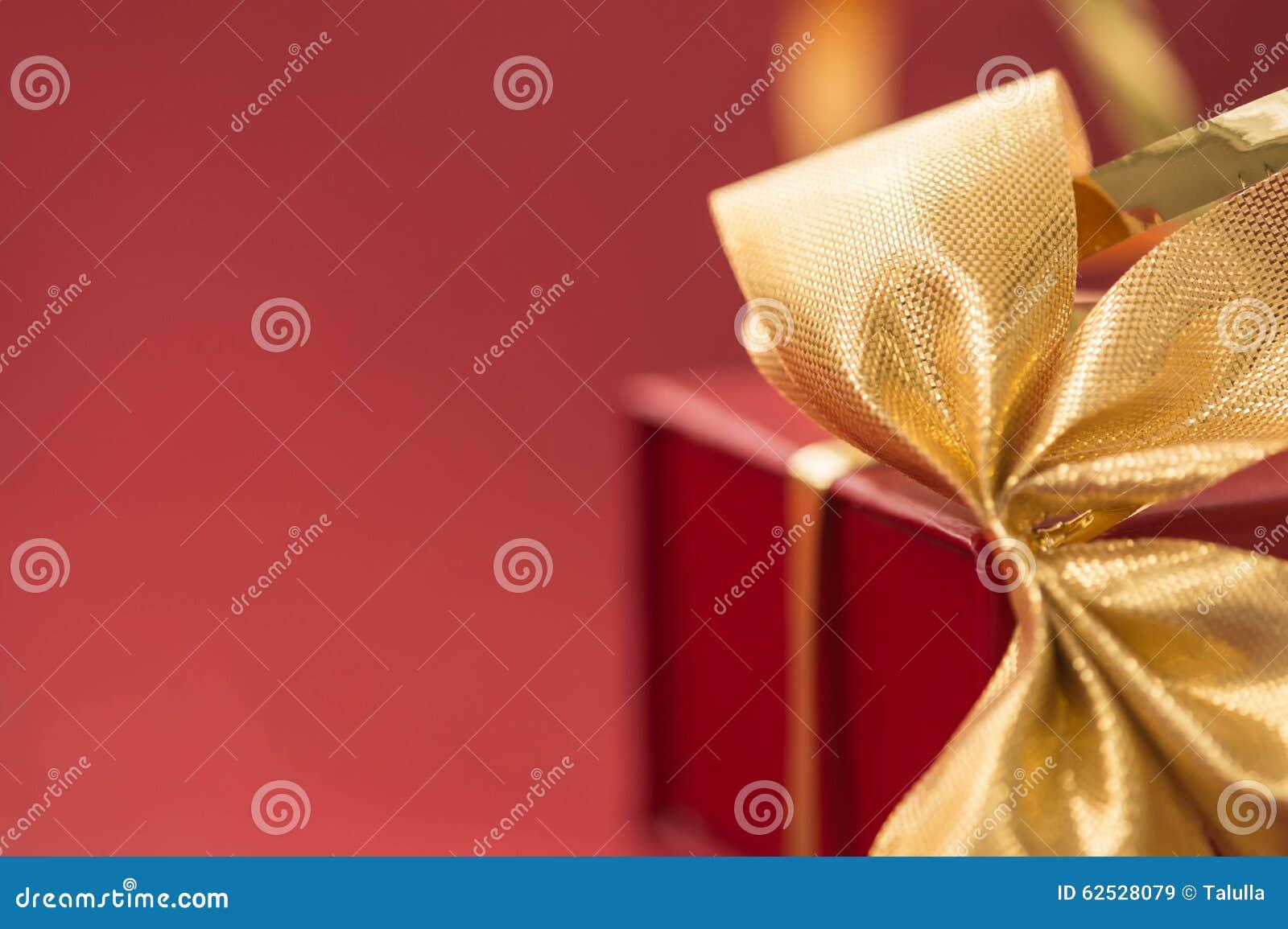 有金黄弓的礼物盒在红色背景
