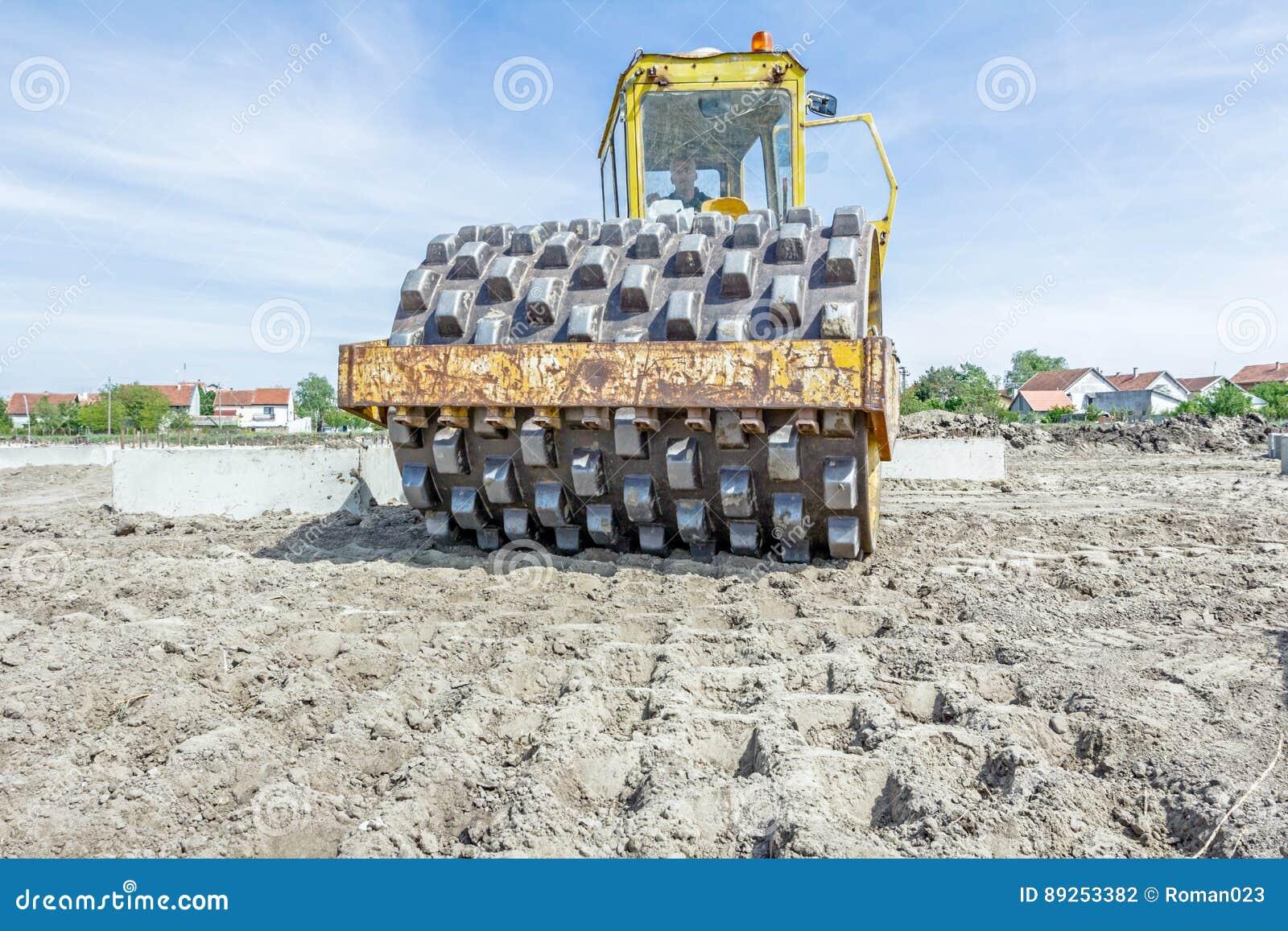 有钉的巨大的压路机在建筑变紧密土壤