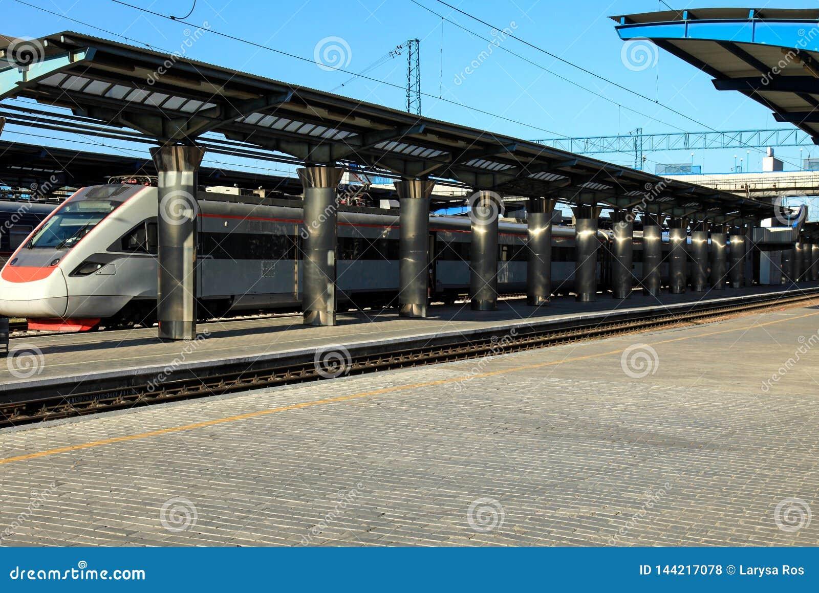 有铁路支架立场的客车在驻地的平台 旅行和旅游业概念、夏天和春天