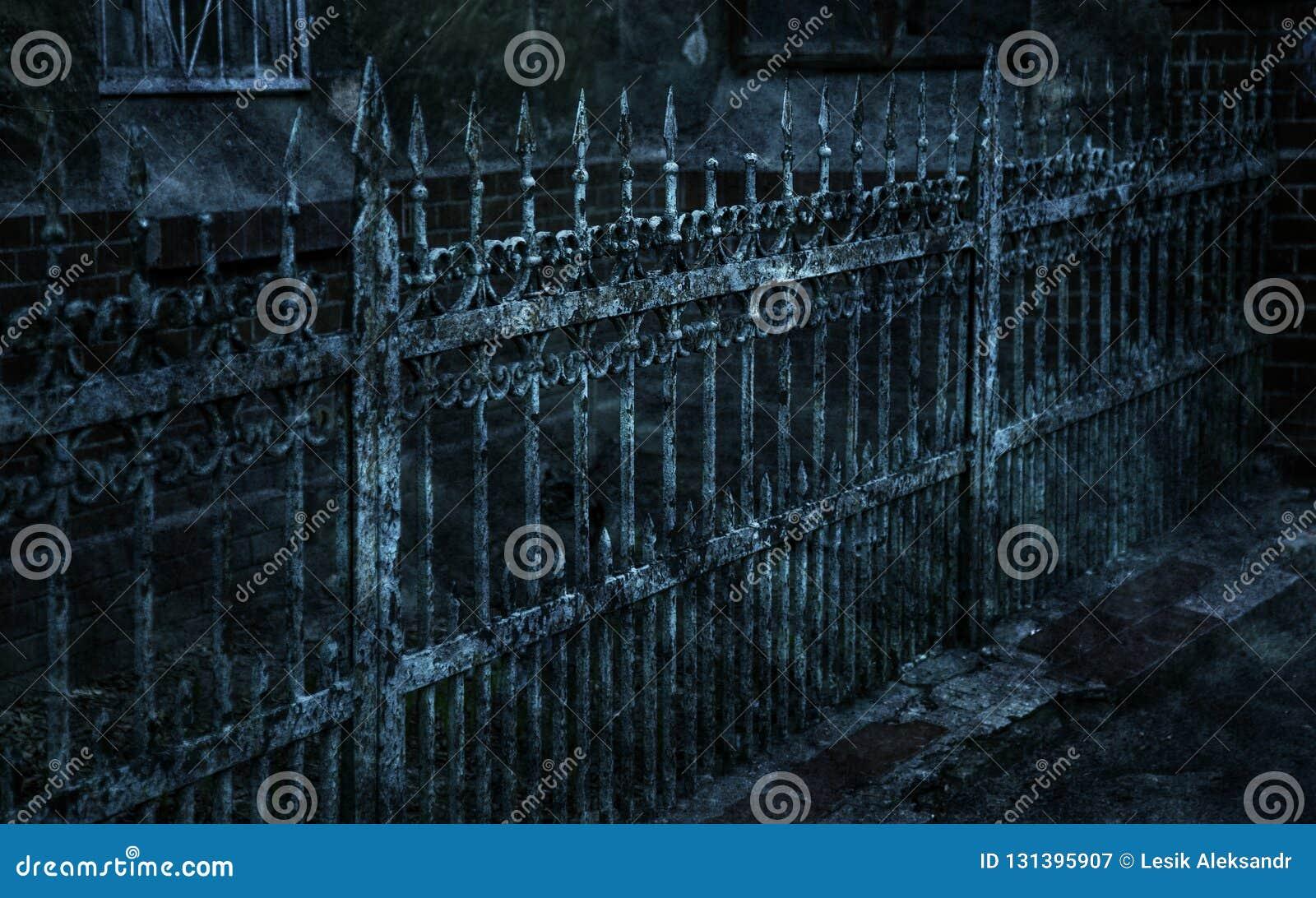 有锋利的矛和破裂的油漆的老伪造的铁生铁篱芭时常 打破的白色肮脏的被放弃的篱芭