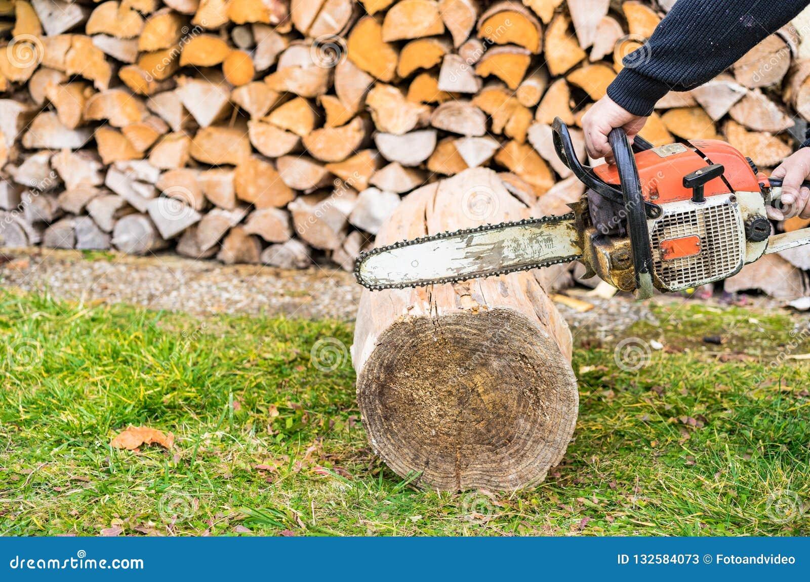 有锯的男性手切开木柴