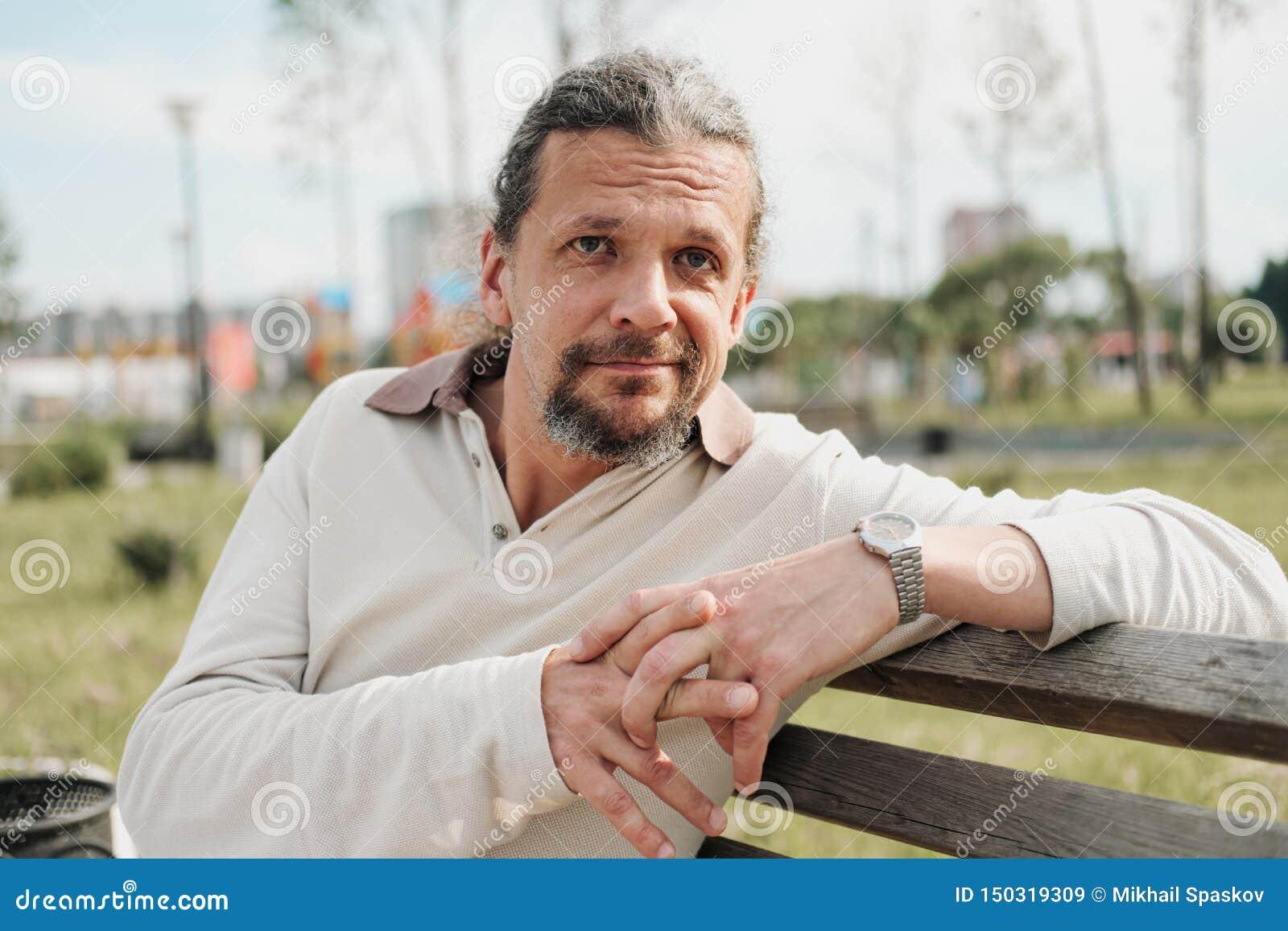 有长发的一个可爱的年长50岁的人在尾巴在一个公园里坐长凳 E