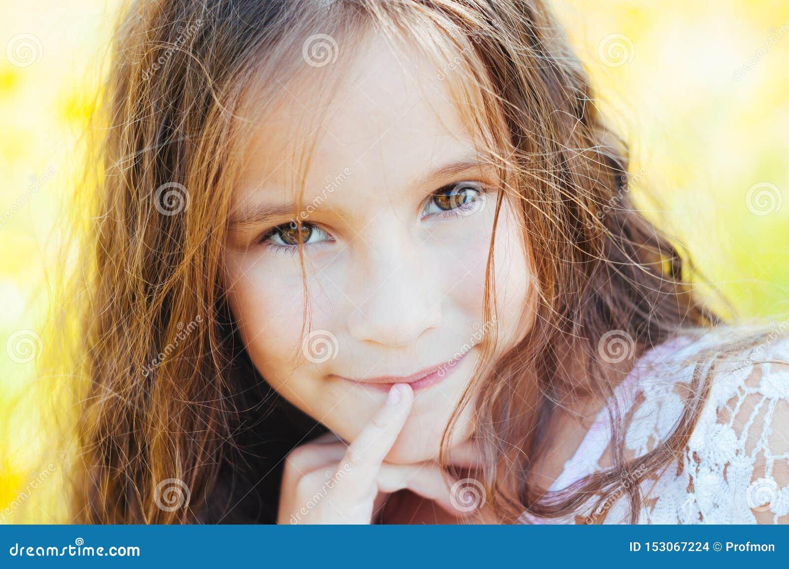 有长发的女孩在一件白色礼服在与花的一个领域高兴