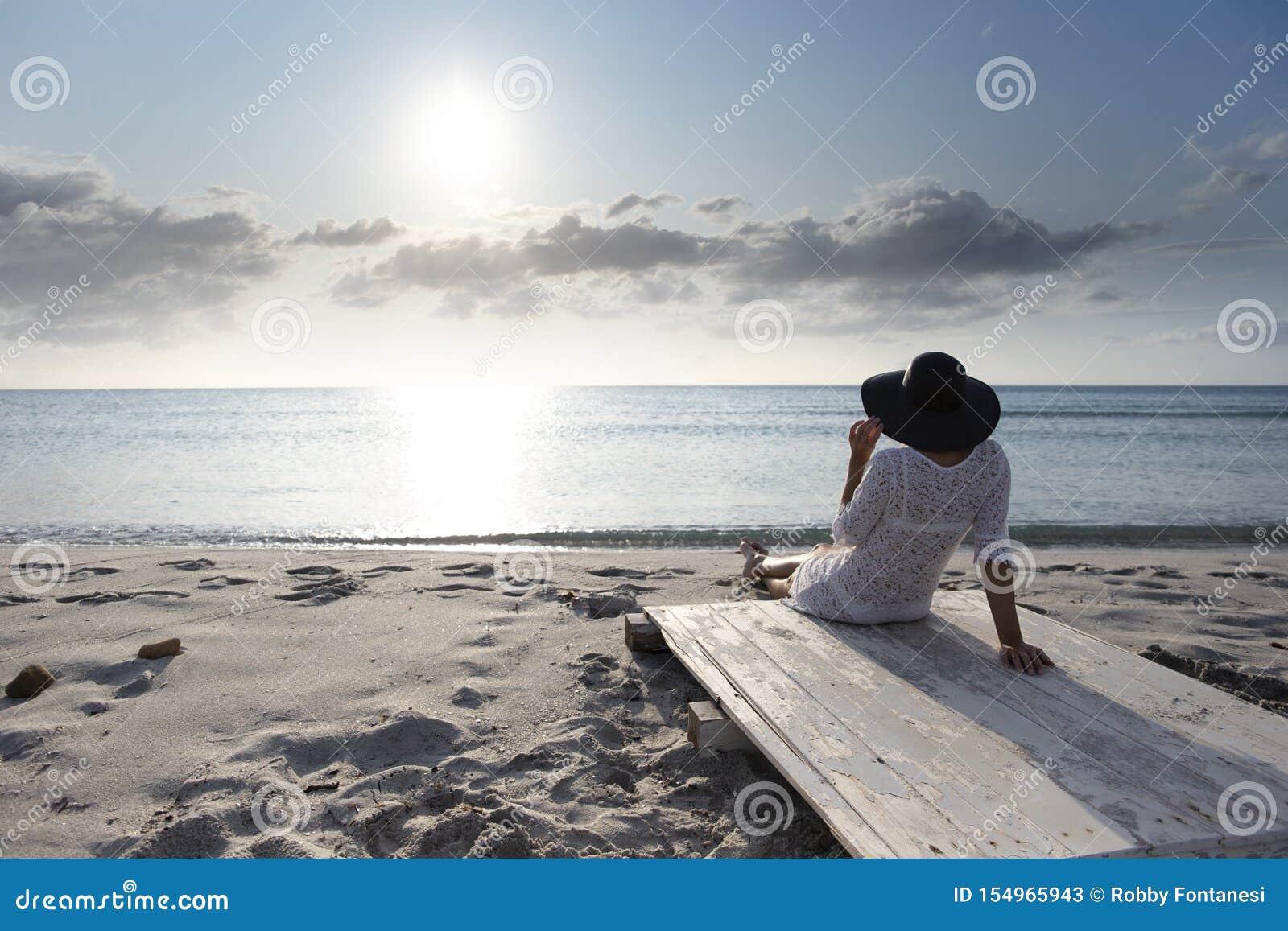 有长发的年轻女人从坐由海看看的后面天际在风的黎明,穿戴在一件白色鞋带礼服