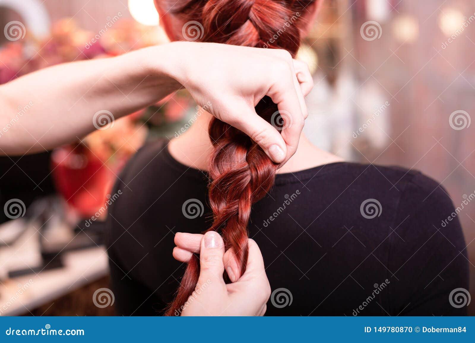 有长发的美丽,红发女孩,美发师编织法国辫子,在发廊 专业护发