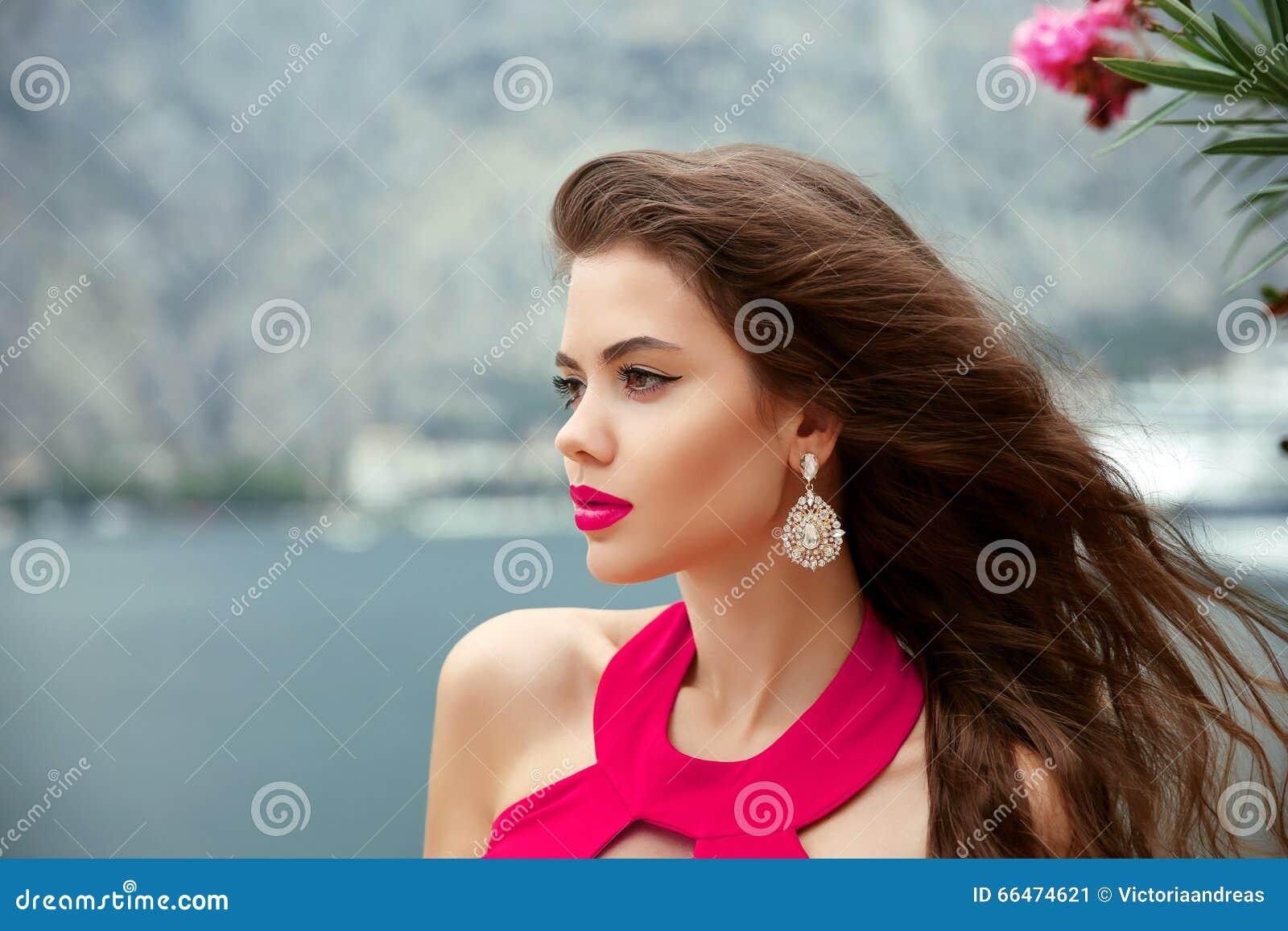 有长的波浪发、红色嘴唇和时尚耳环的美丽的女孩