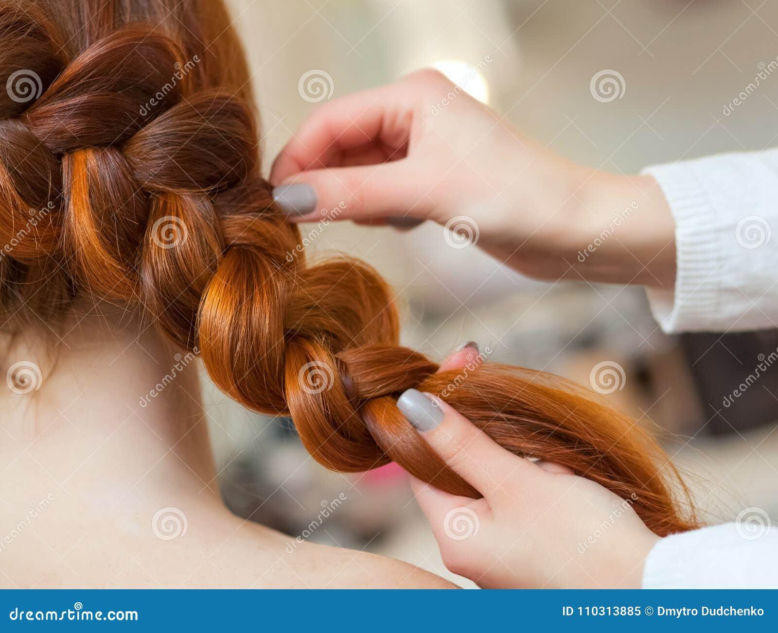 有长的红色头发的美丽的女孩,美发师编织一条辫子,在美容院