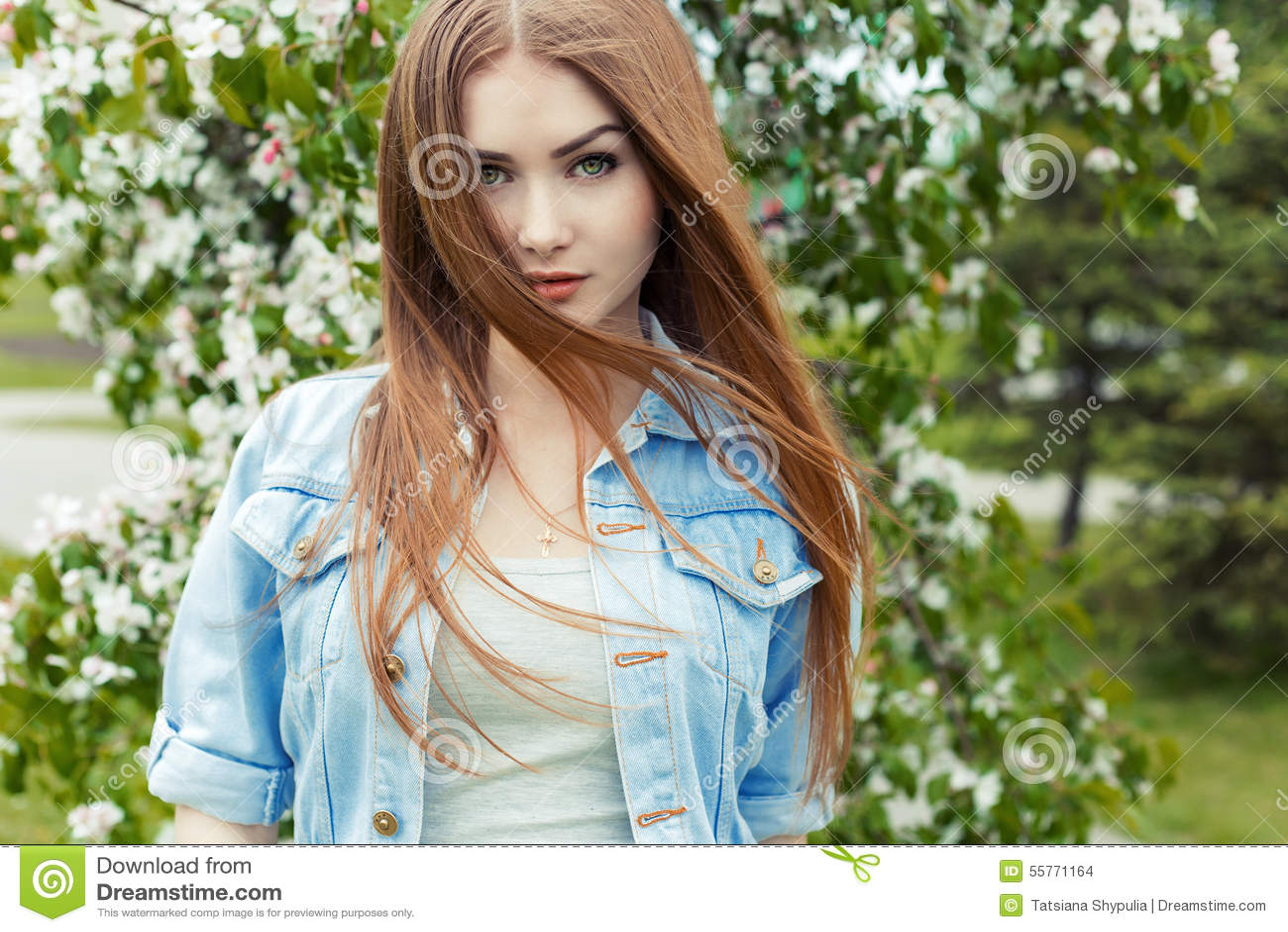 有长的红色头发和嫉妒的美丽的性感的逗人喜爱的甜女孩在开花的树附近的一件牛仔布夹克在公园风