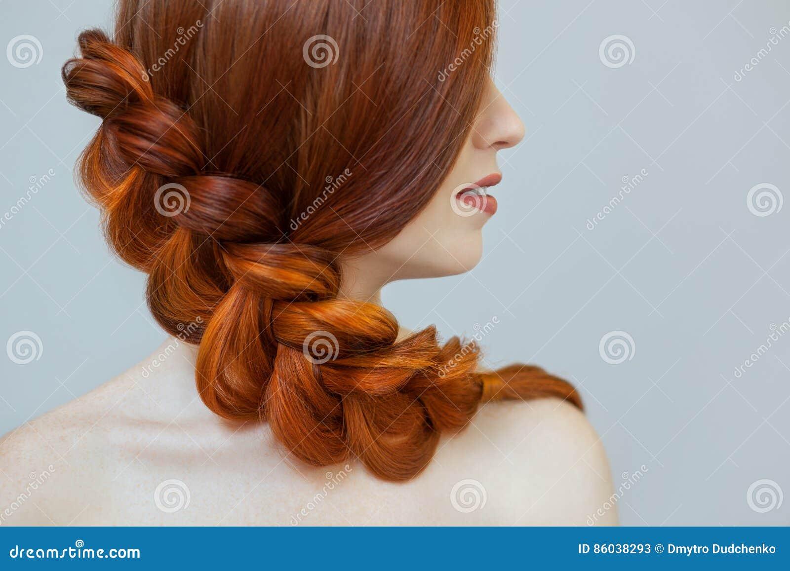 有长的红色头发的美丽的女孩,编辫子与法国辫子,在美容院