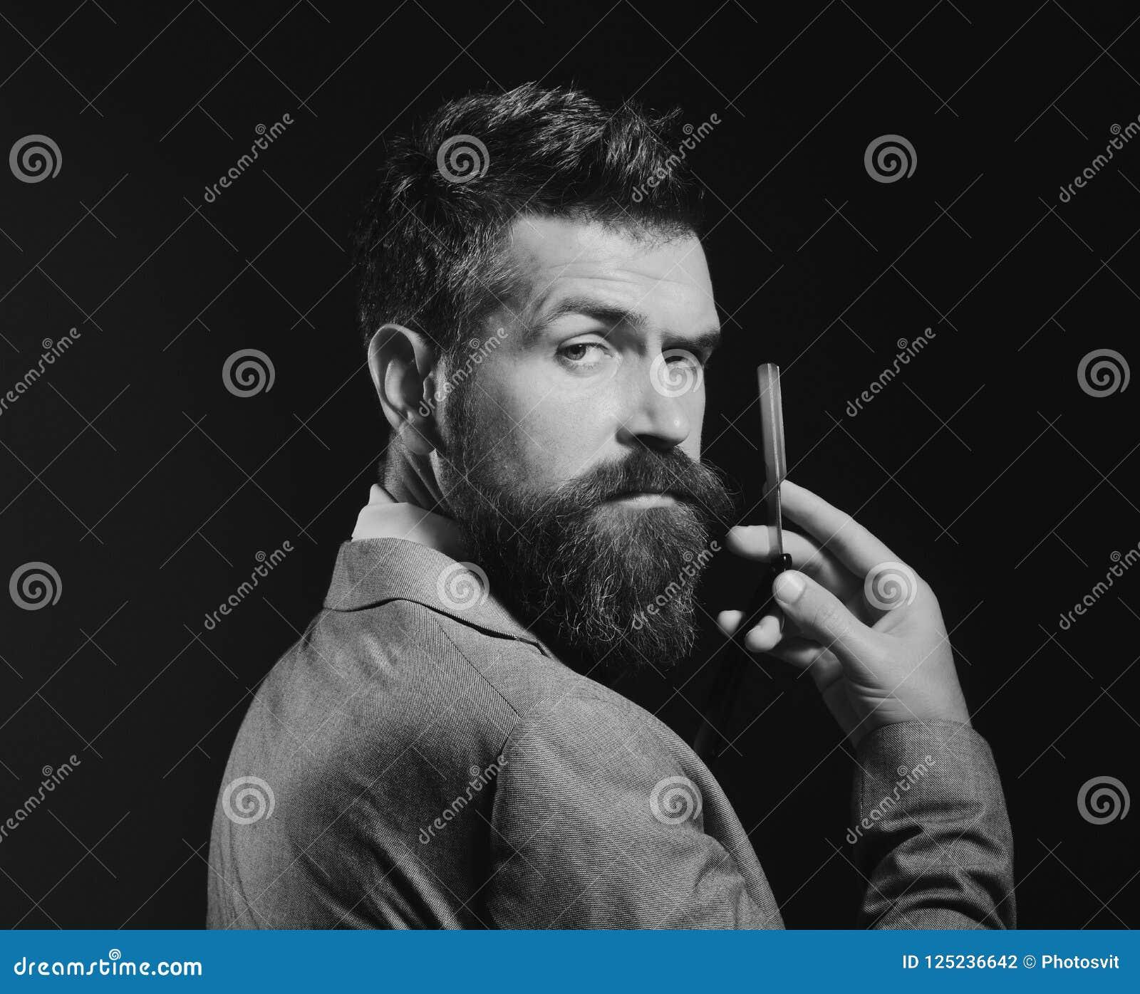 有长的胡子的人拿着剃刀的刀片 理发店广告