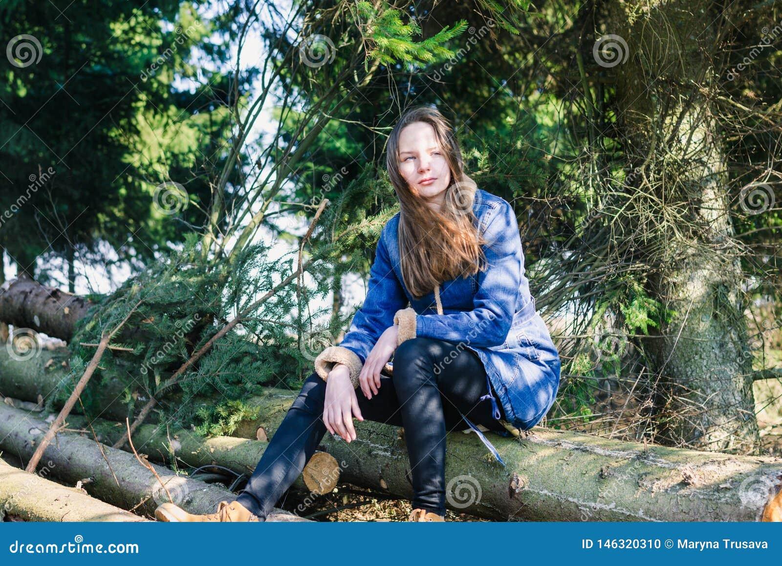 有长的金发和牛仔布夹克的一少女坐注册一个绿色具球果森林在一个温暖的晴朗的春日