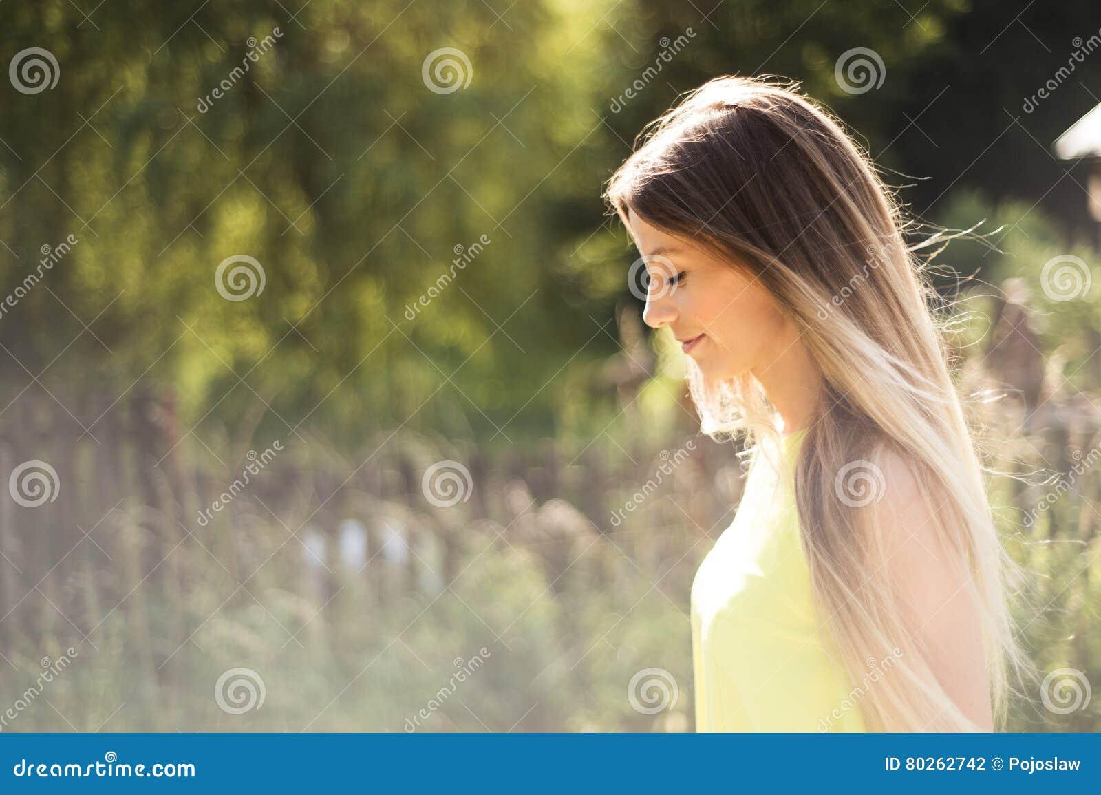 有长的金发的美丽的少妇 晴朗的夏天