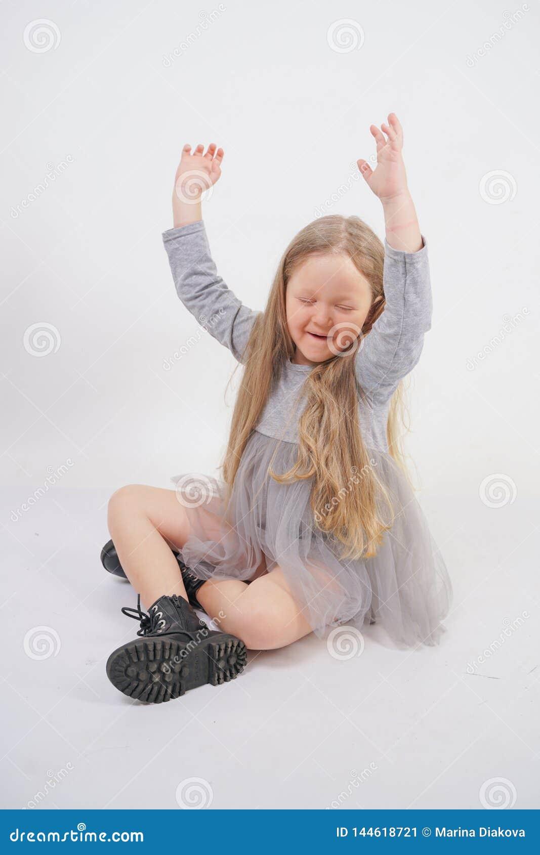 有长的金发的逗人喜爱的女孩孩子甜甜地坐地板和哈欠,伸她的手用在白色的不同的方向