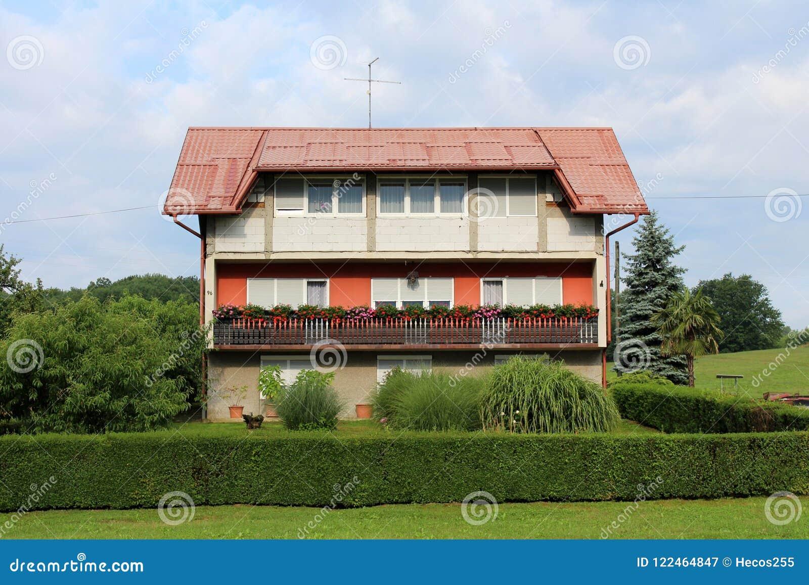 有长的阳台的大部分地未完成的郊区家庭房子包围与草和树