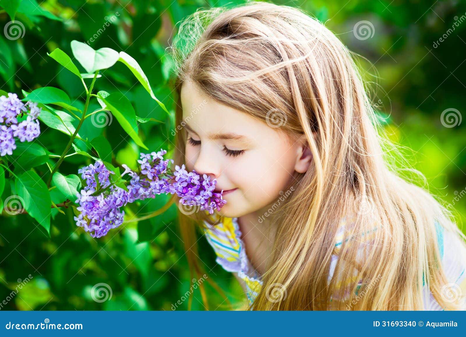 有长的头发嗅到的花的美丽的白肤金发的小女孩