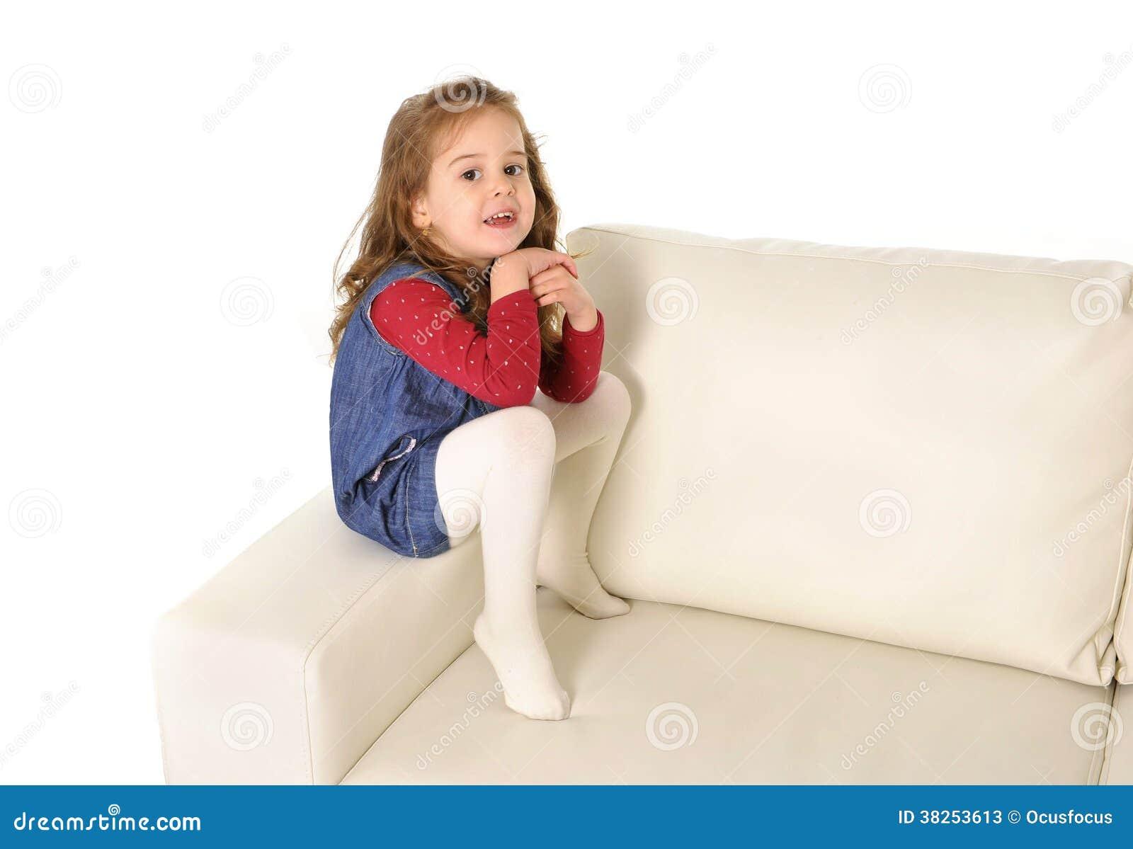 有长的头发的愉快的可爱的小女孩坐长沙发的胳膊