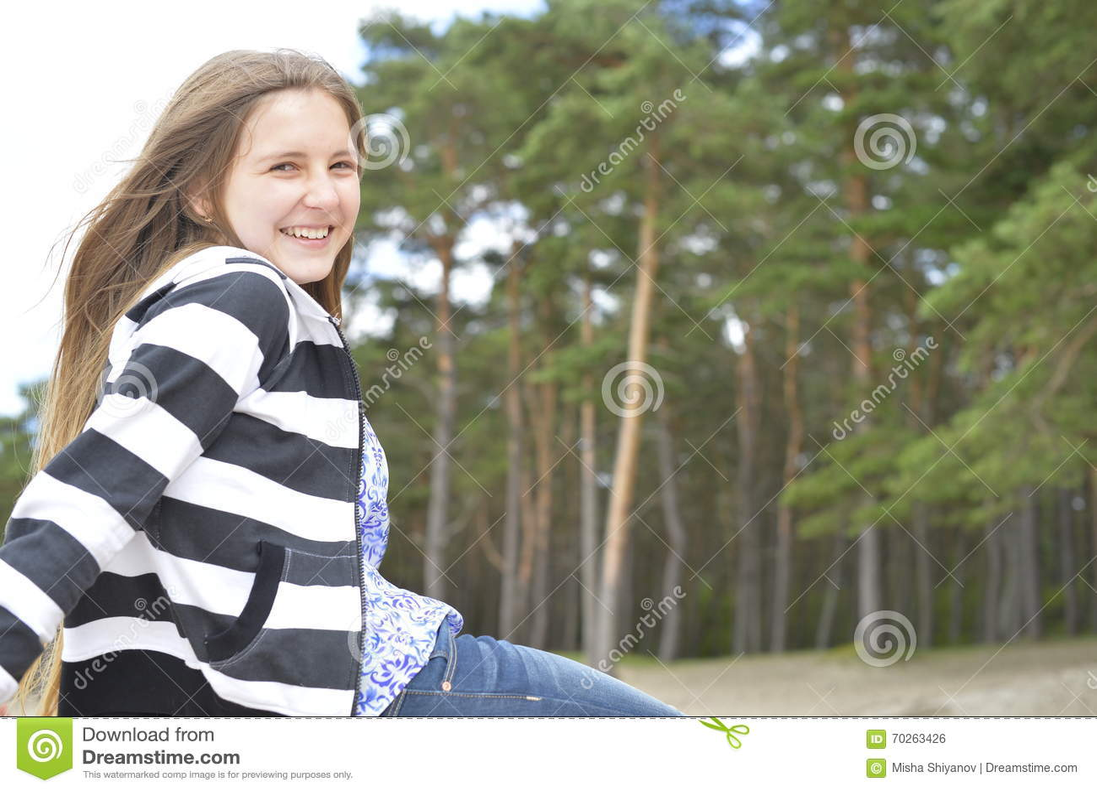 有长的头发的白肤金发的女孩坐并且微笑着