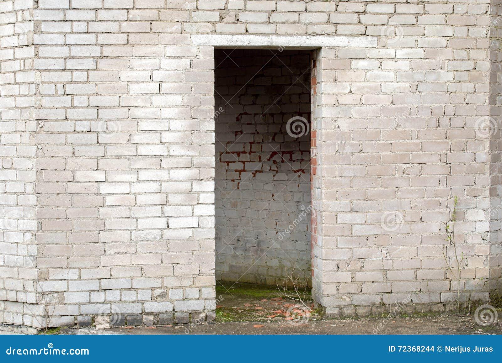 有门道入口的白色破裂的砖墙
